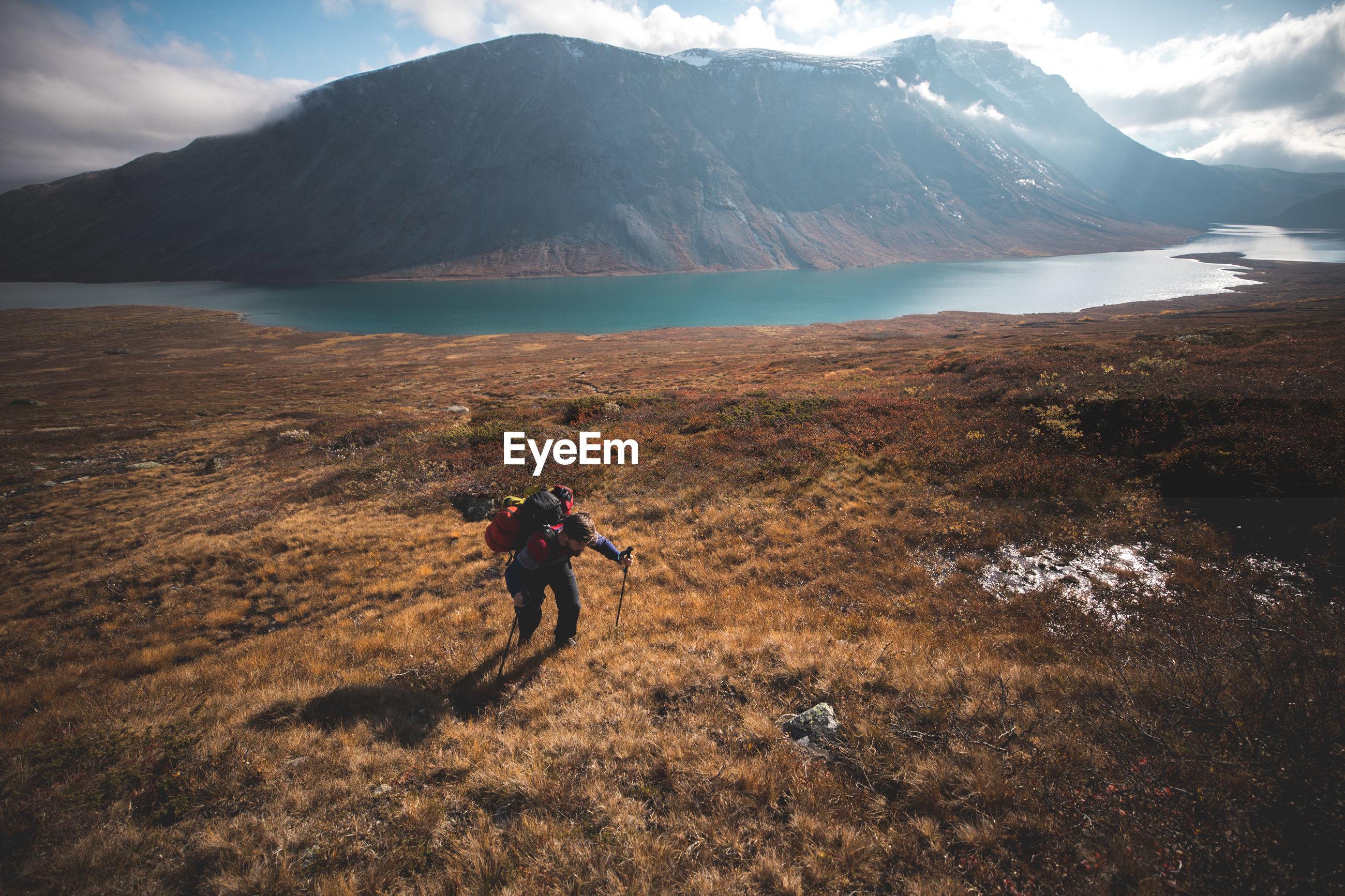 Man climbing on mountain against lake