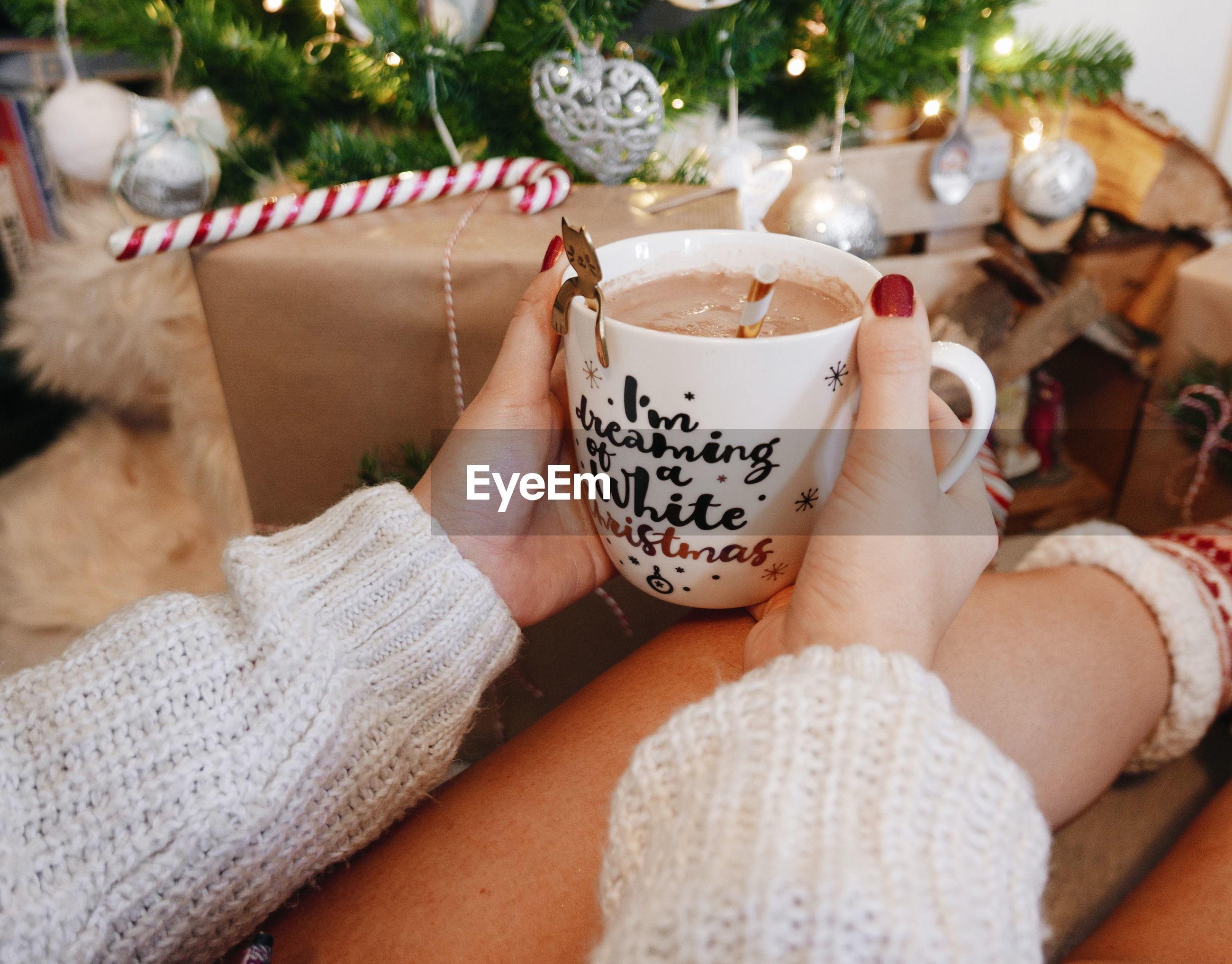 Midsection of woman holding christmas mug.