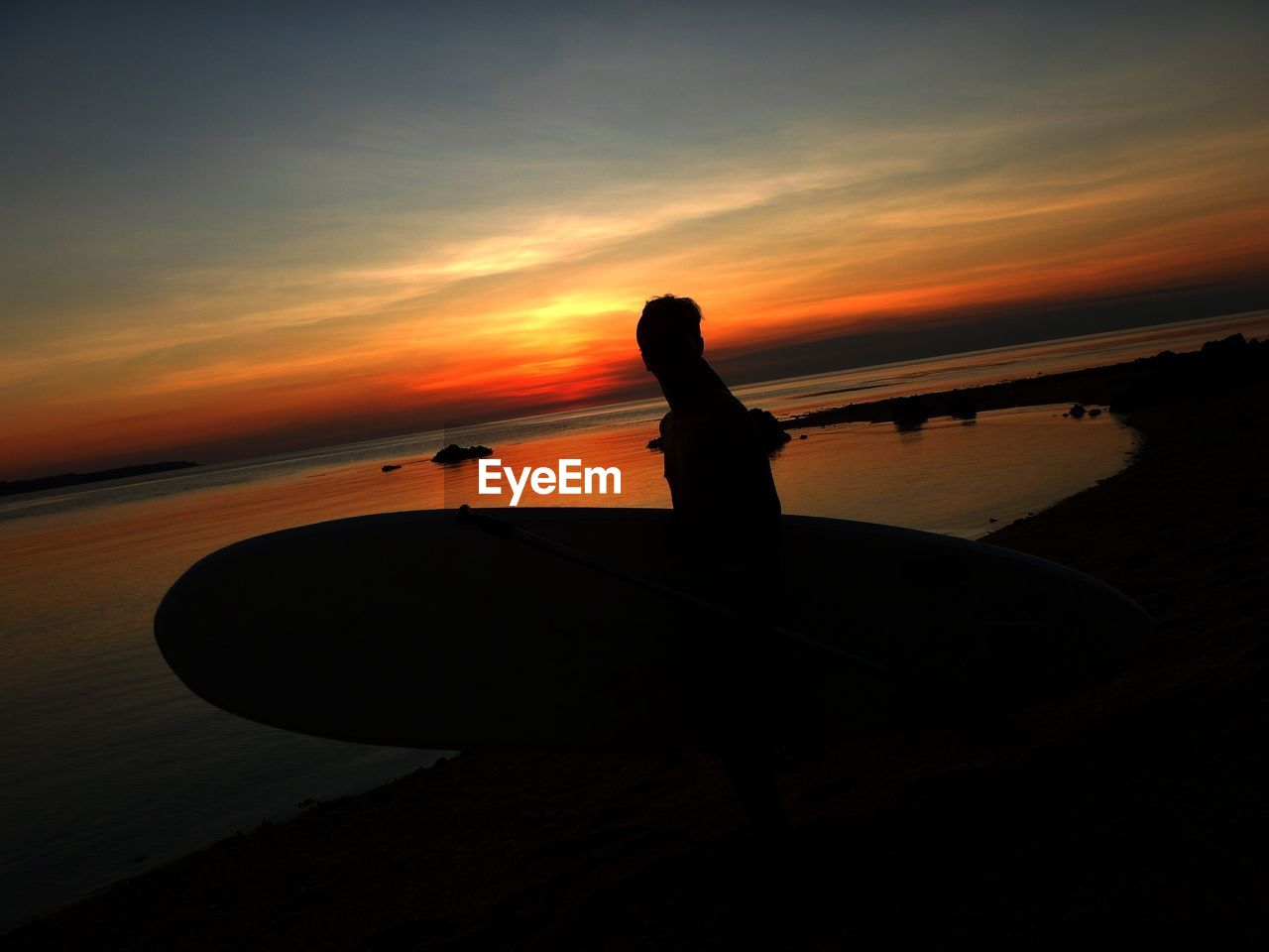 Silhouette Man With Surfboard At Beach Against Sky During Sunset