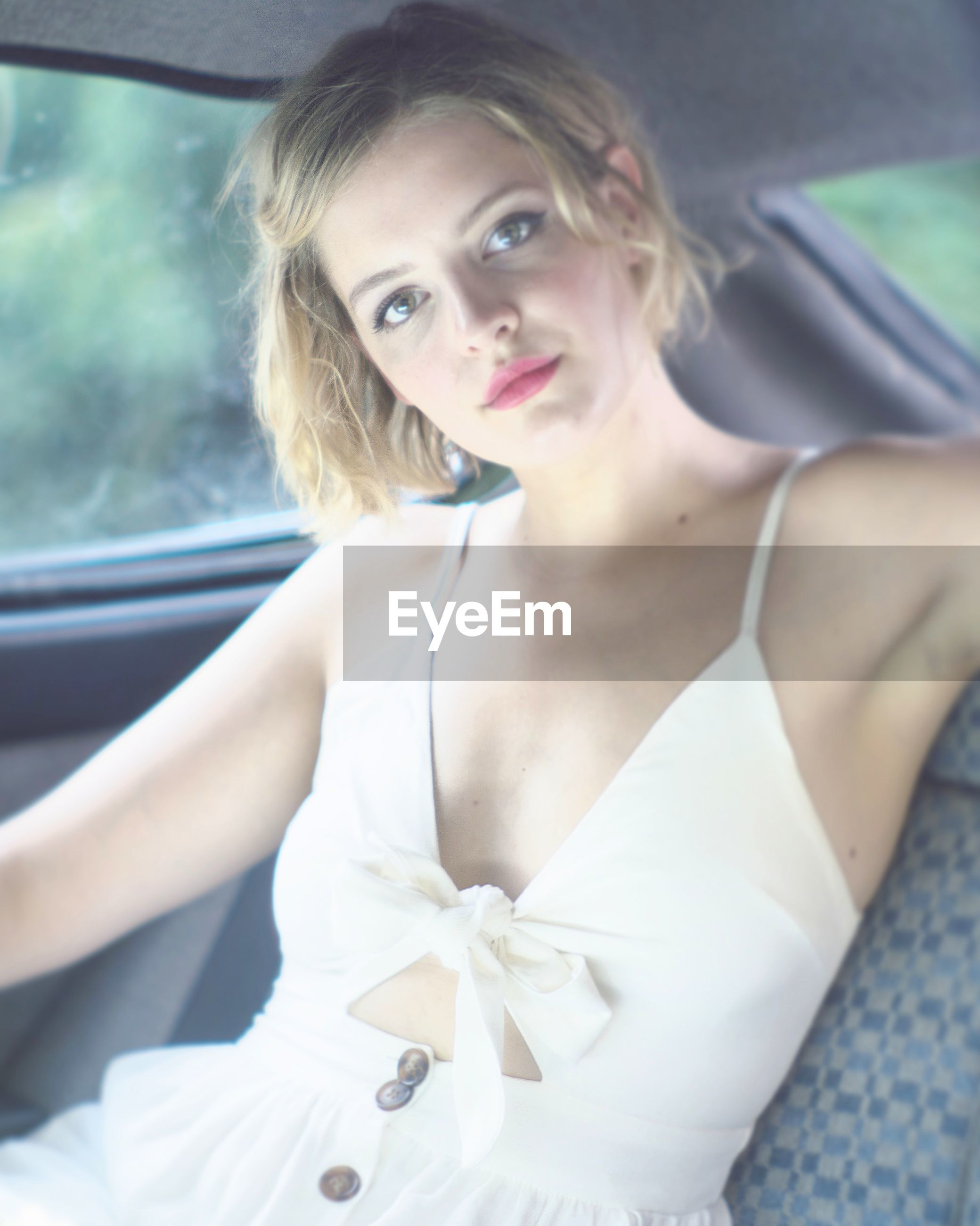 Portrait of fashionable young woman sitting in car