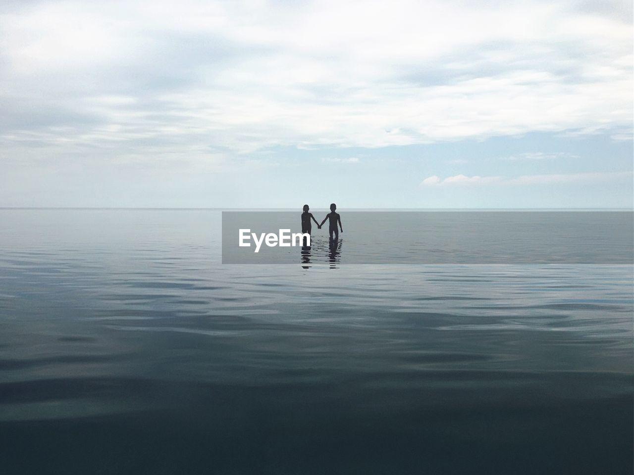 Siblings wading in sea against sky