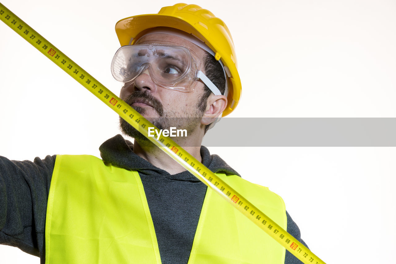 Architect measuring with tape measure against white background