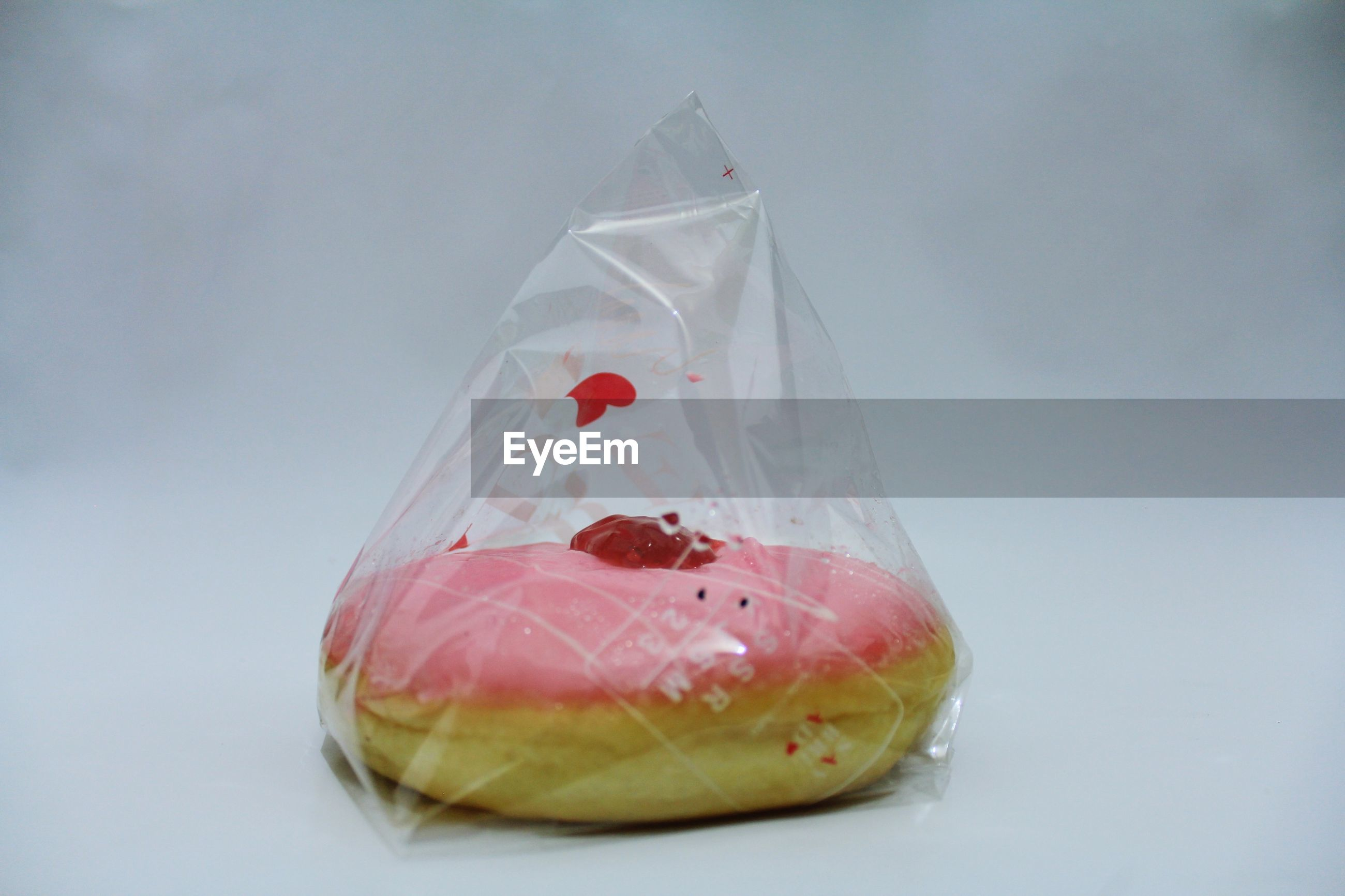 Close-up of donut in plastic over gray background