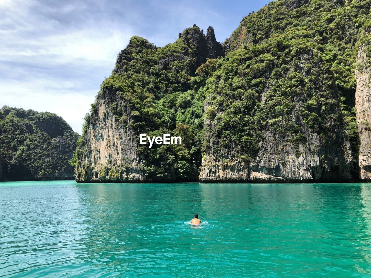 Man swimming in sea against mountains
