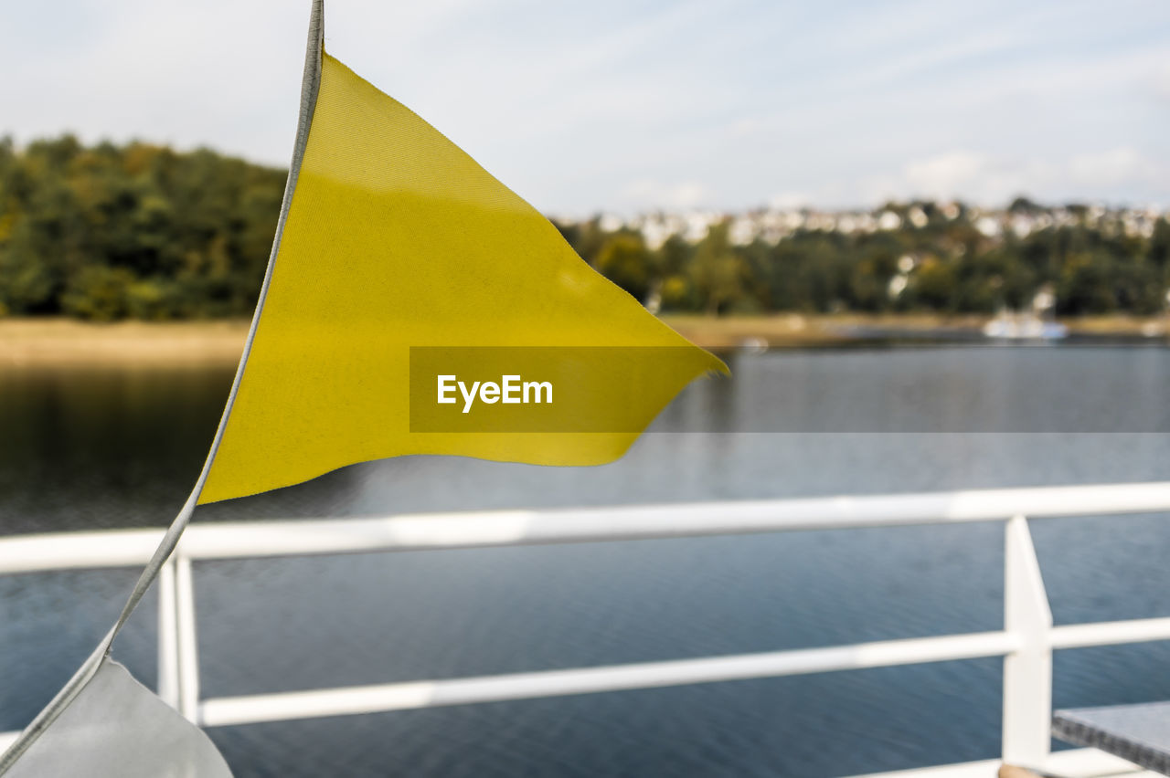 yellow, water, focus on foreground, no people, flag, day, nature, sea, sunlight, outdoors, sky, close-up, shape, nautical vessel, sunny, transportation, pole