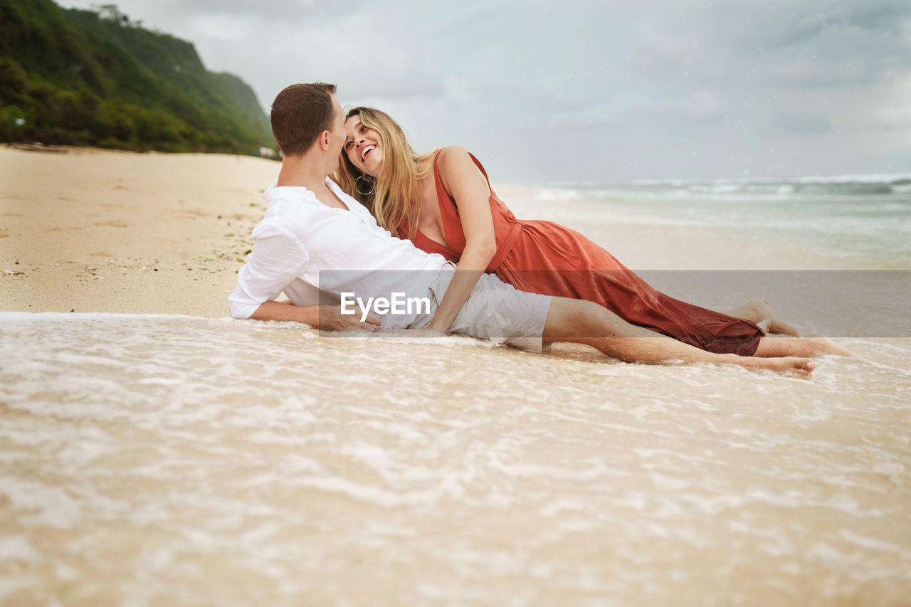 Happy young couple romancing while lying at shore