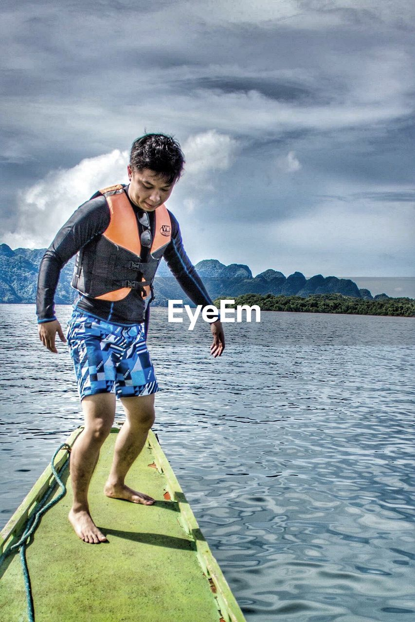water, full length, real people, one person, sky, leisure activity, outdoors, nature, day, cloud - sky, casual clothing, scenics, lifestyles, lake, front view, beauty in nature, mountain, mid-air, standing, young adult, vacations, people