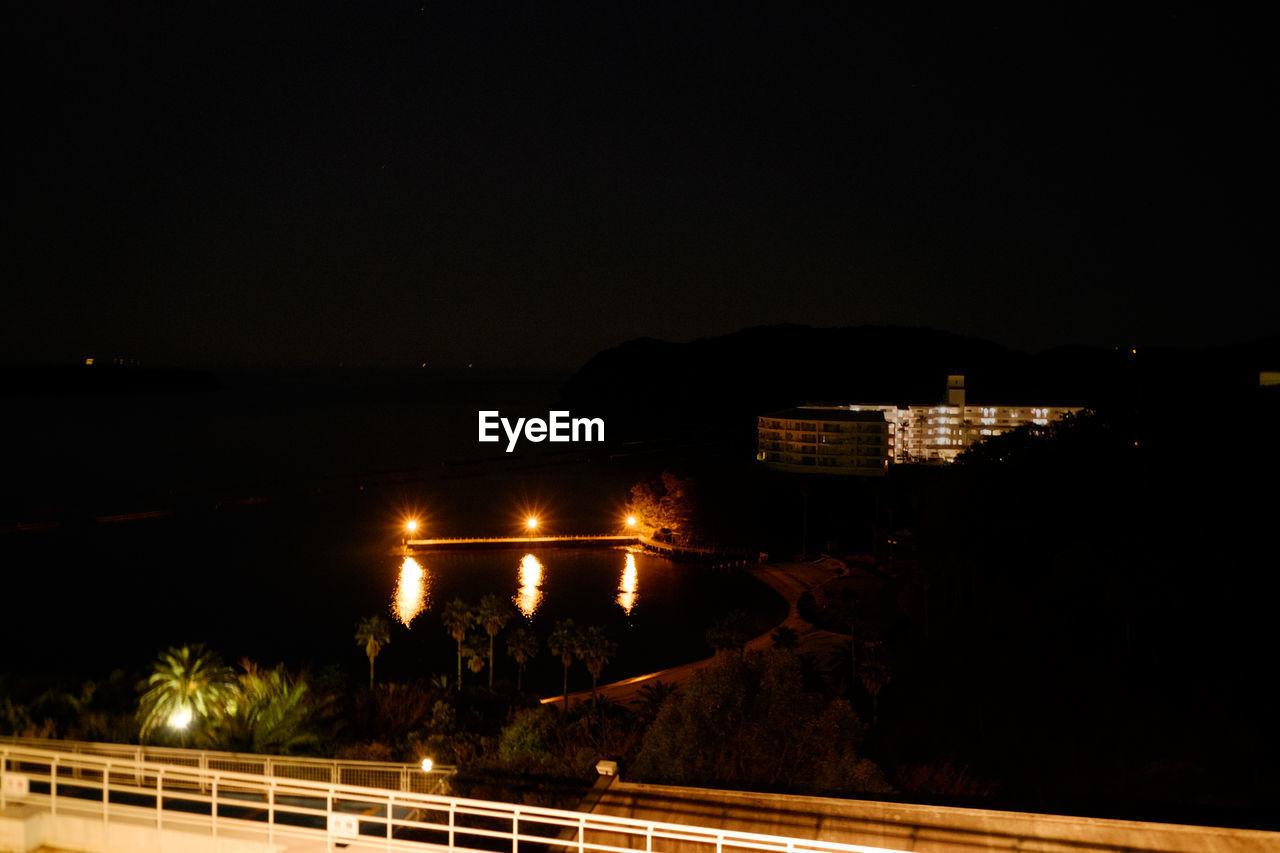 Illuminated building against sky seen from bridge at night