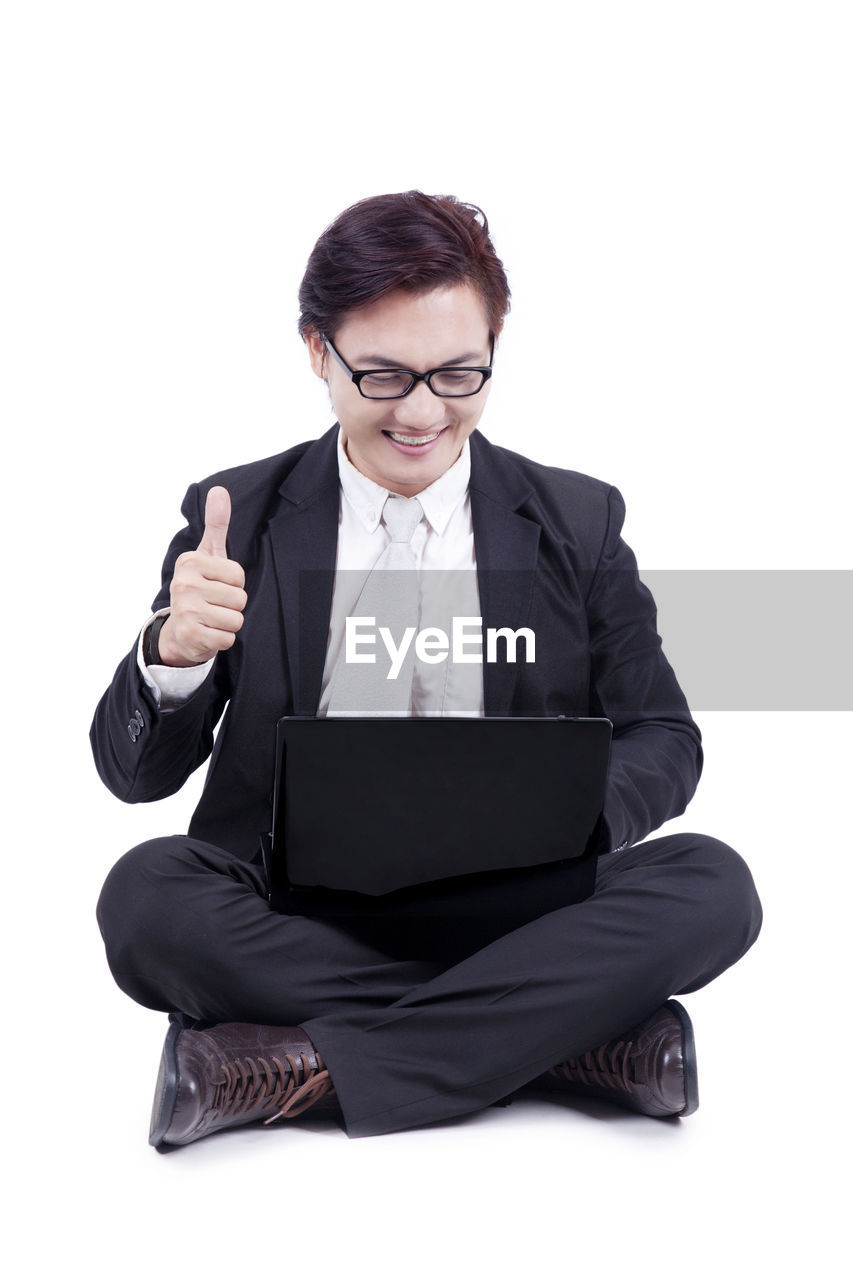 glasses, one person, white background, front view, technology, cut out, sitting, wireless technology, eyeglasses, laptop, indoors, communication, young adult, computer, studio shot, full length, cross-legged, formalwear, business, connection, using laptop, hairstyle