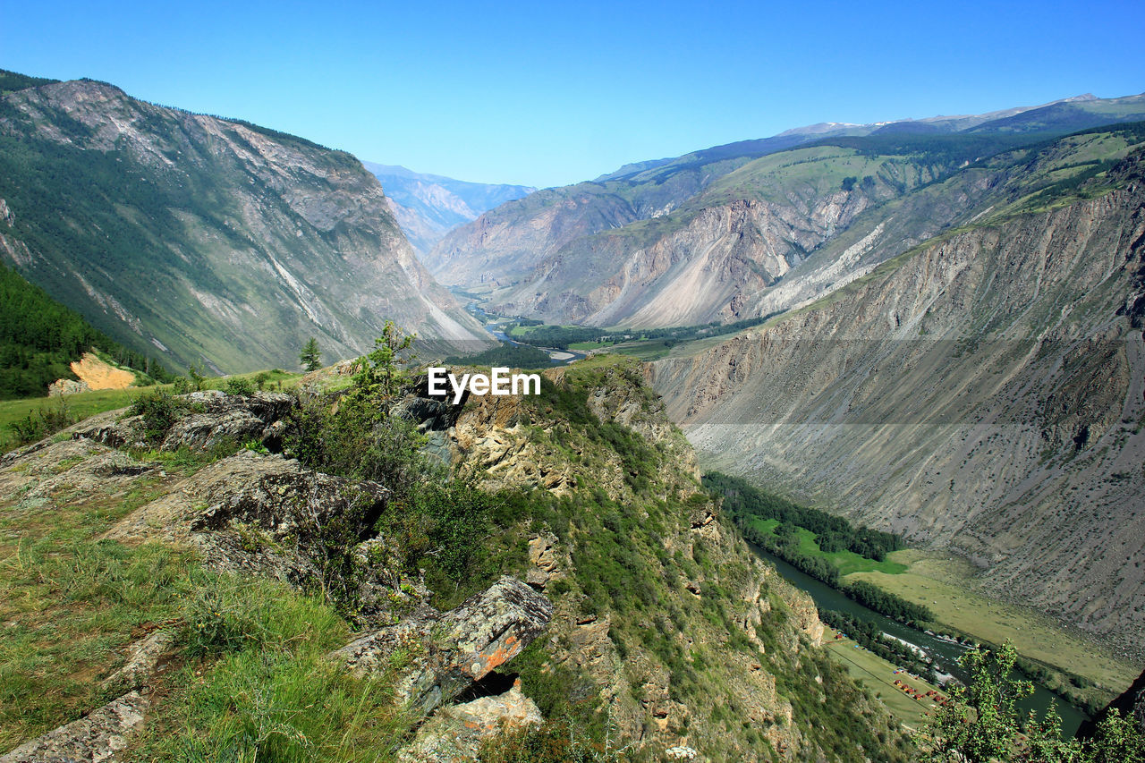 Rocky mountain slope overlooking the high-mountain chulyshman valley with the river in summer
