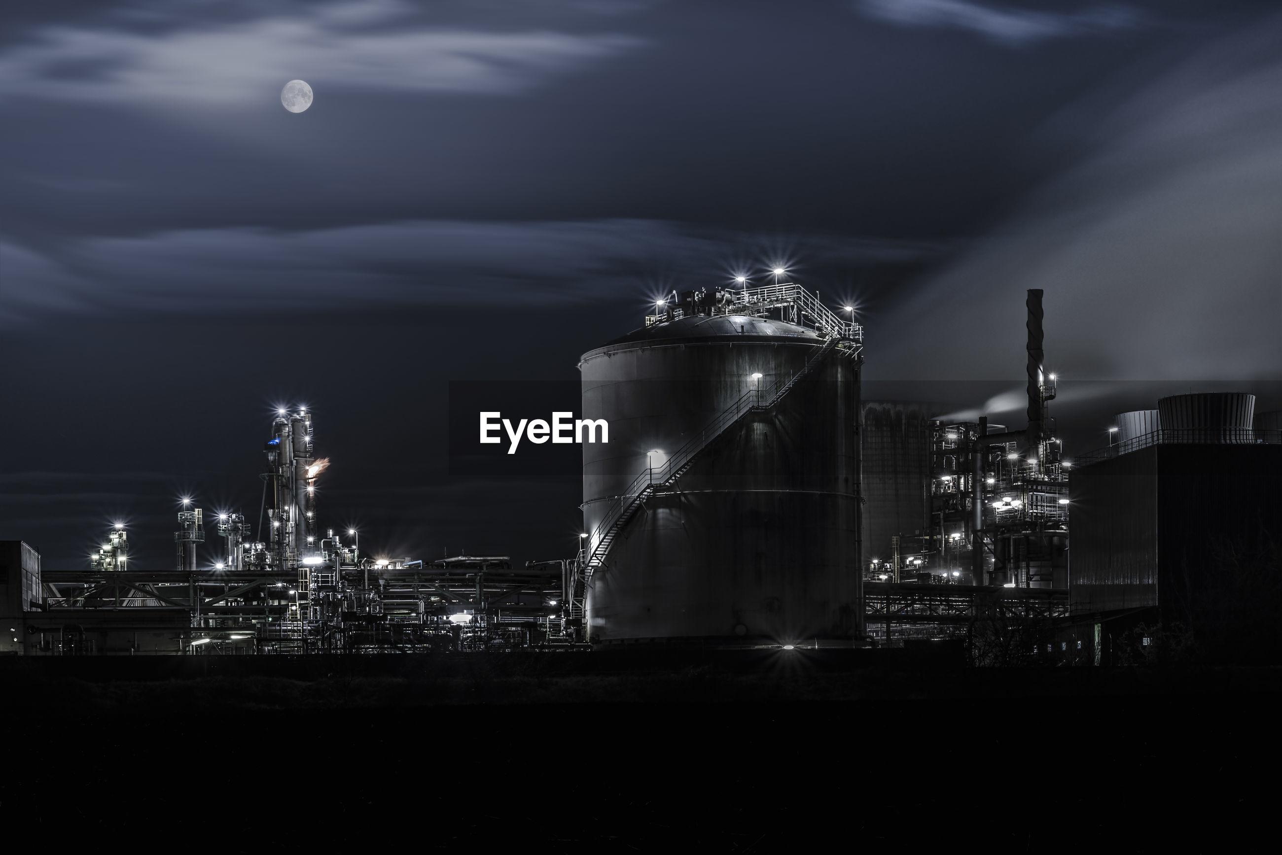 Illuminated factory against sky at night
