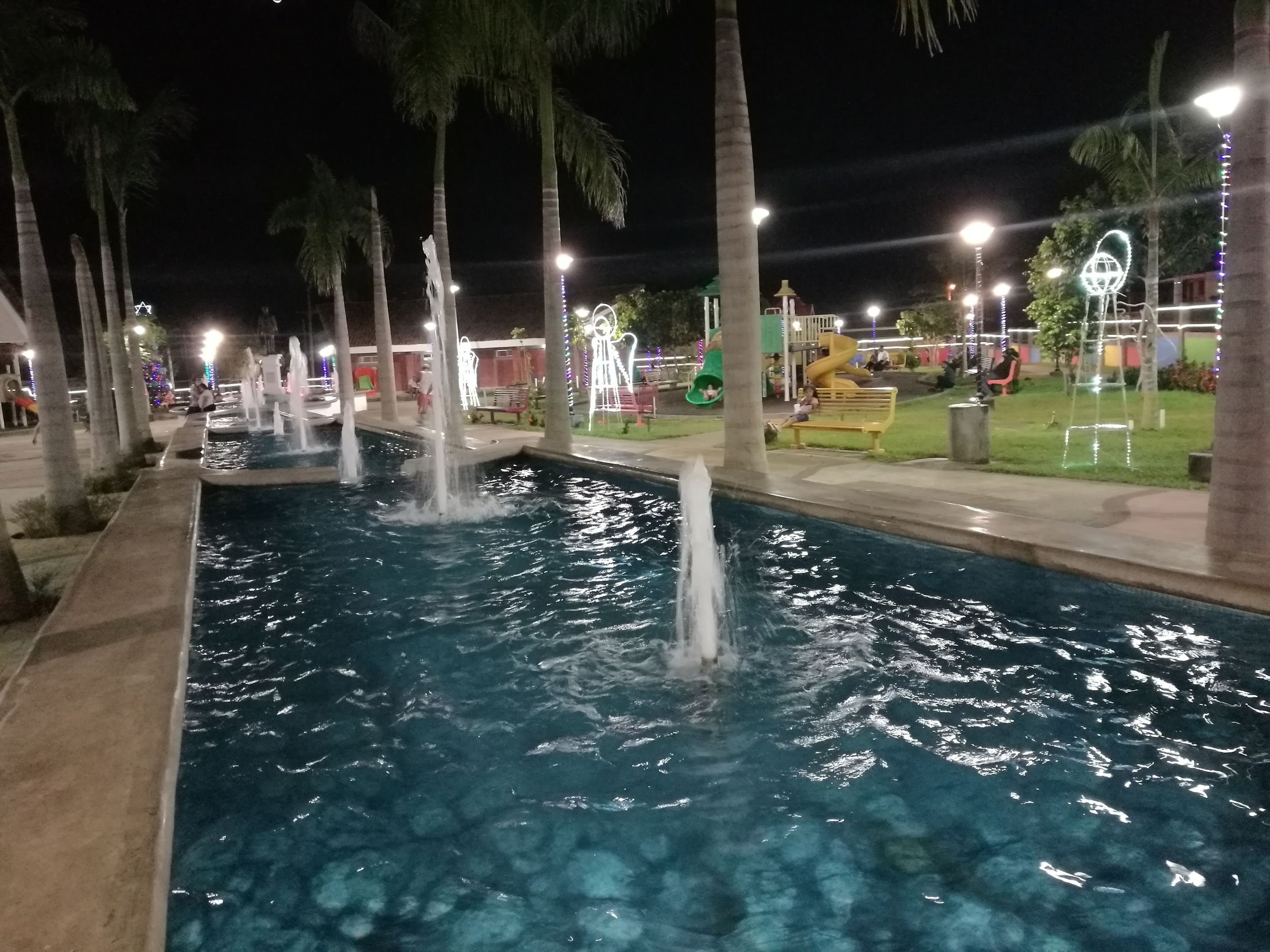 water, swimming pool, night, illuminated, real people, outdoors, water park, long exposure, waterfront, tree, large group of people, motion, men, palm tree, building exterior, spraying, architecture, nature, water slide, people