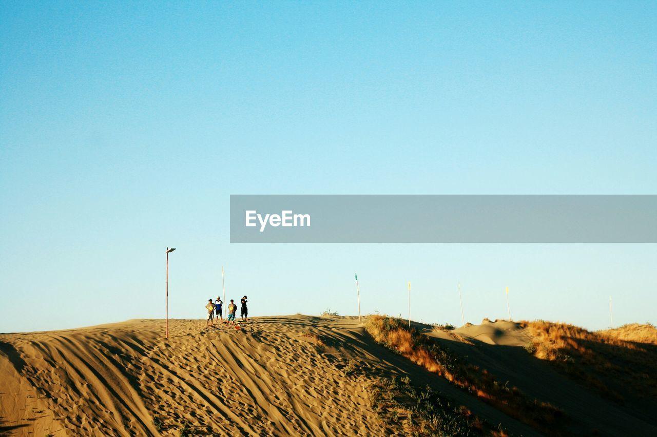 People standing on sand dune