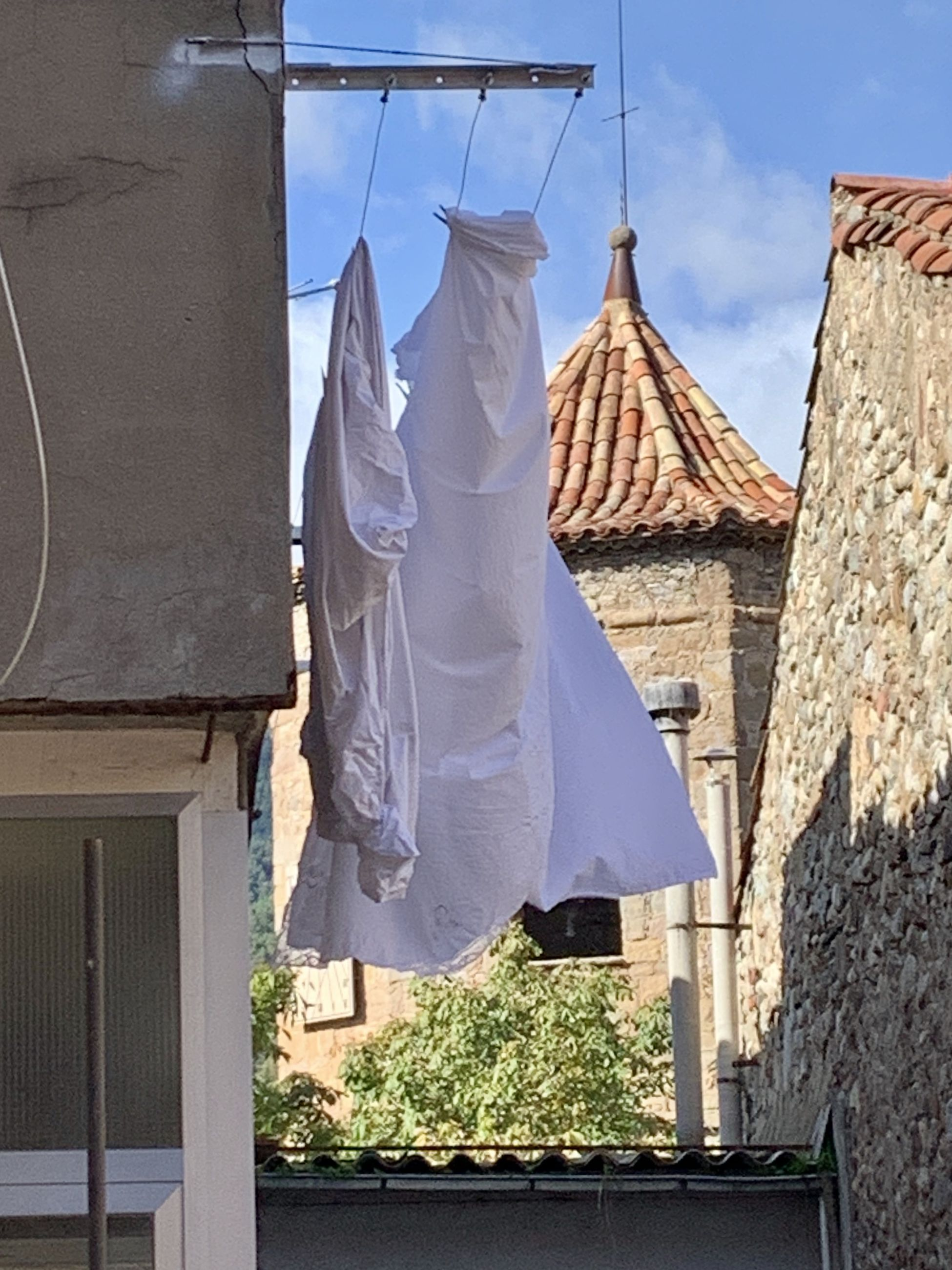 LOW ANGLE VIEW OF CLOTHES DRYING ON CLOTHESLINE AGAINST BUILDING