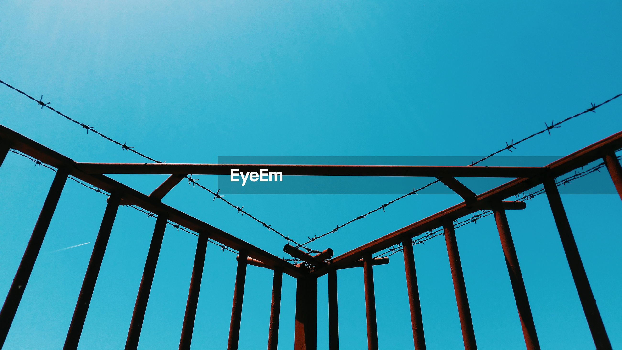 Low angle view of metallic railings against clear sky