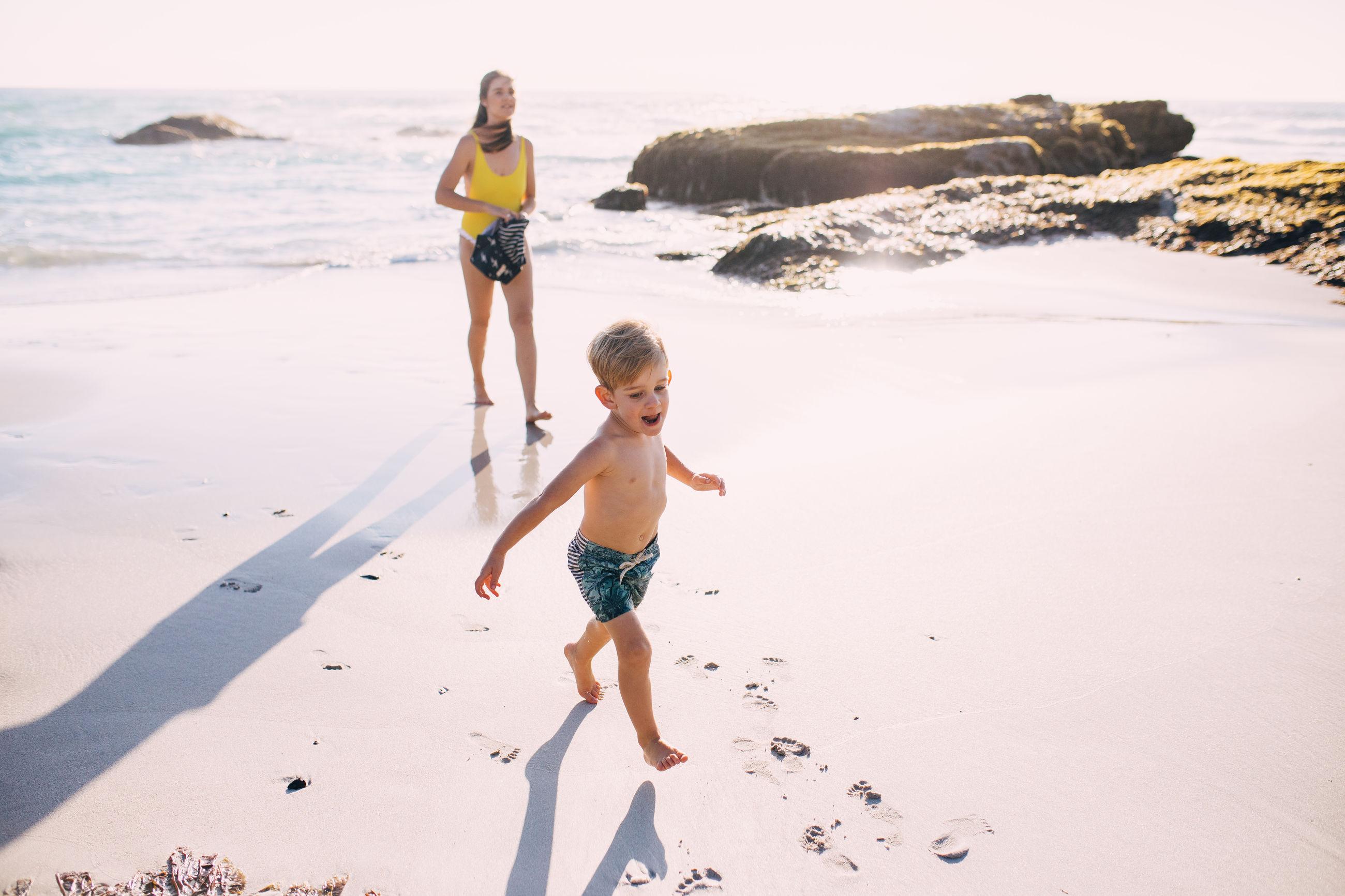 Mother with son enjoying on beach against sky