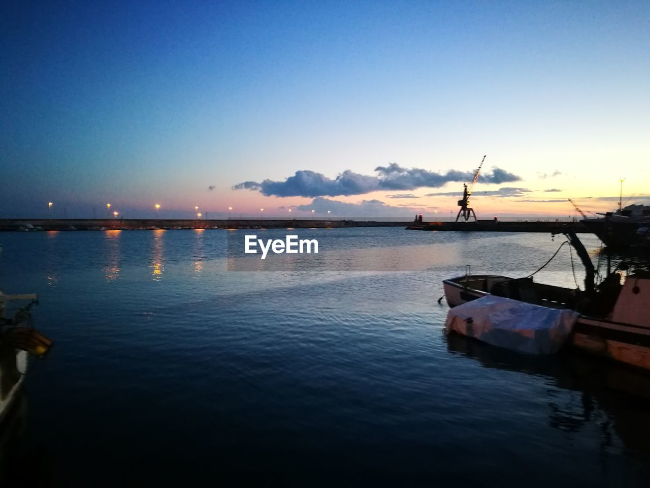 water, nautical vessel, sunset, transportation, sky, reflection, mode of transport, nature, sea, waterfront, beauty in nature, tranquility, scenics, tranquil scene, outdoors, moored, silhouette, blue, no people, industry, day