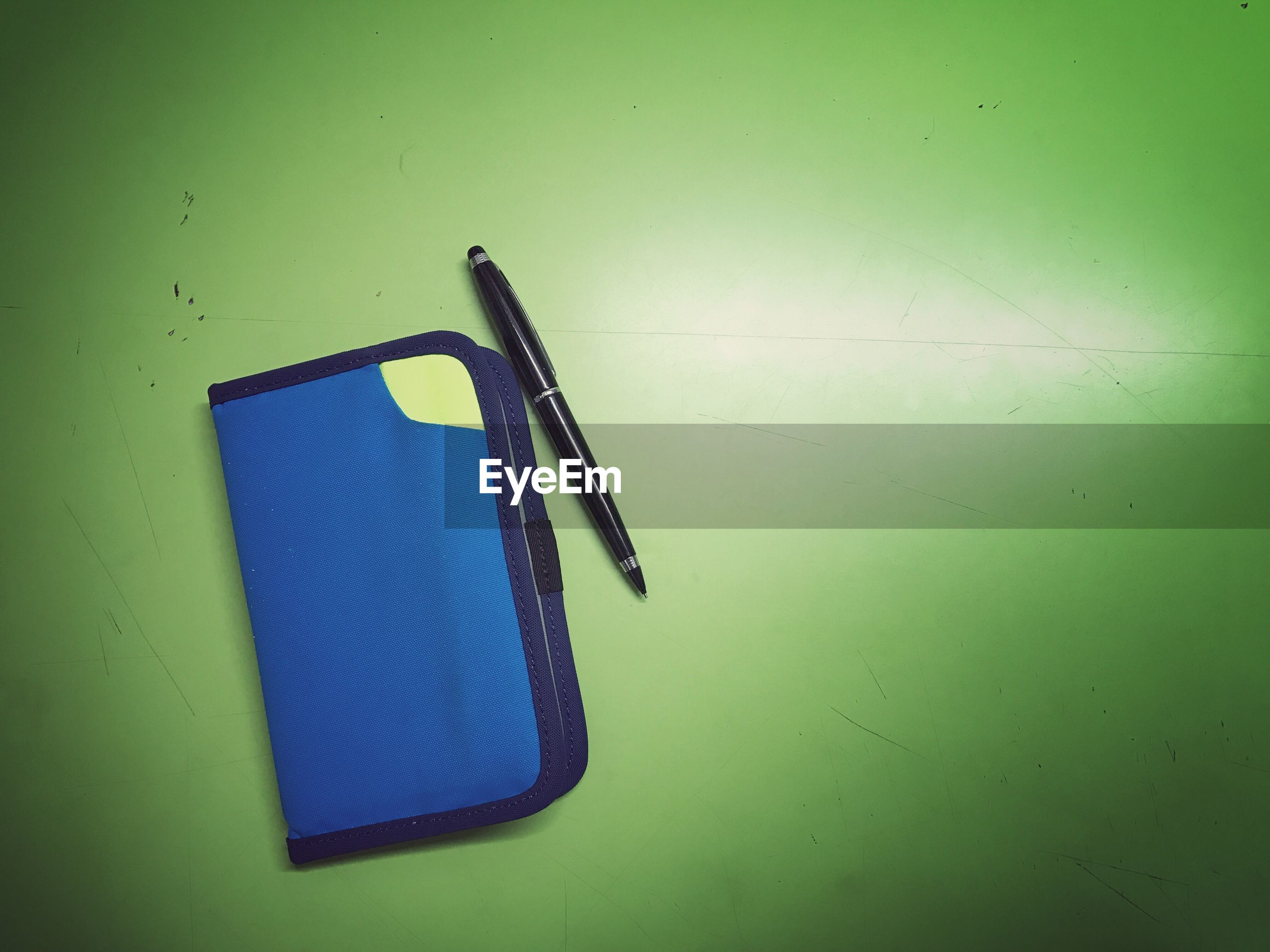 High angle view of pen and wallet on green table