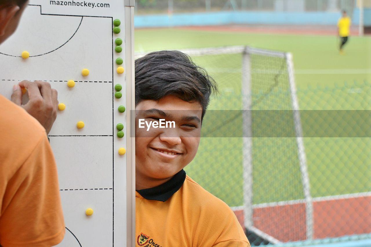 Portrait Of Happy Teenage Boy Standing By Whiteboard