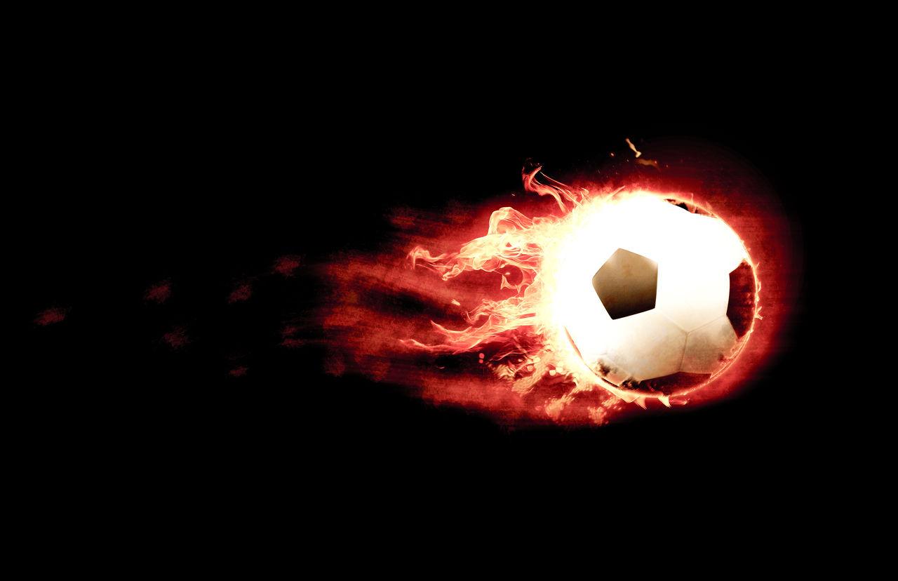 Digital composite image of burning soccer ball over black background