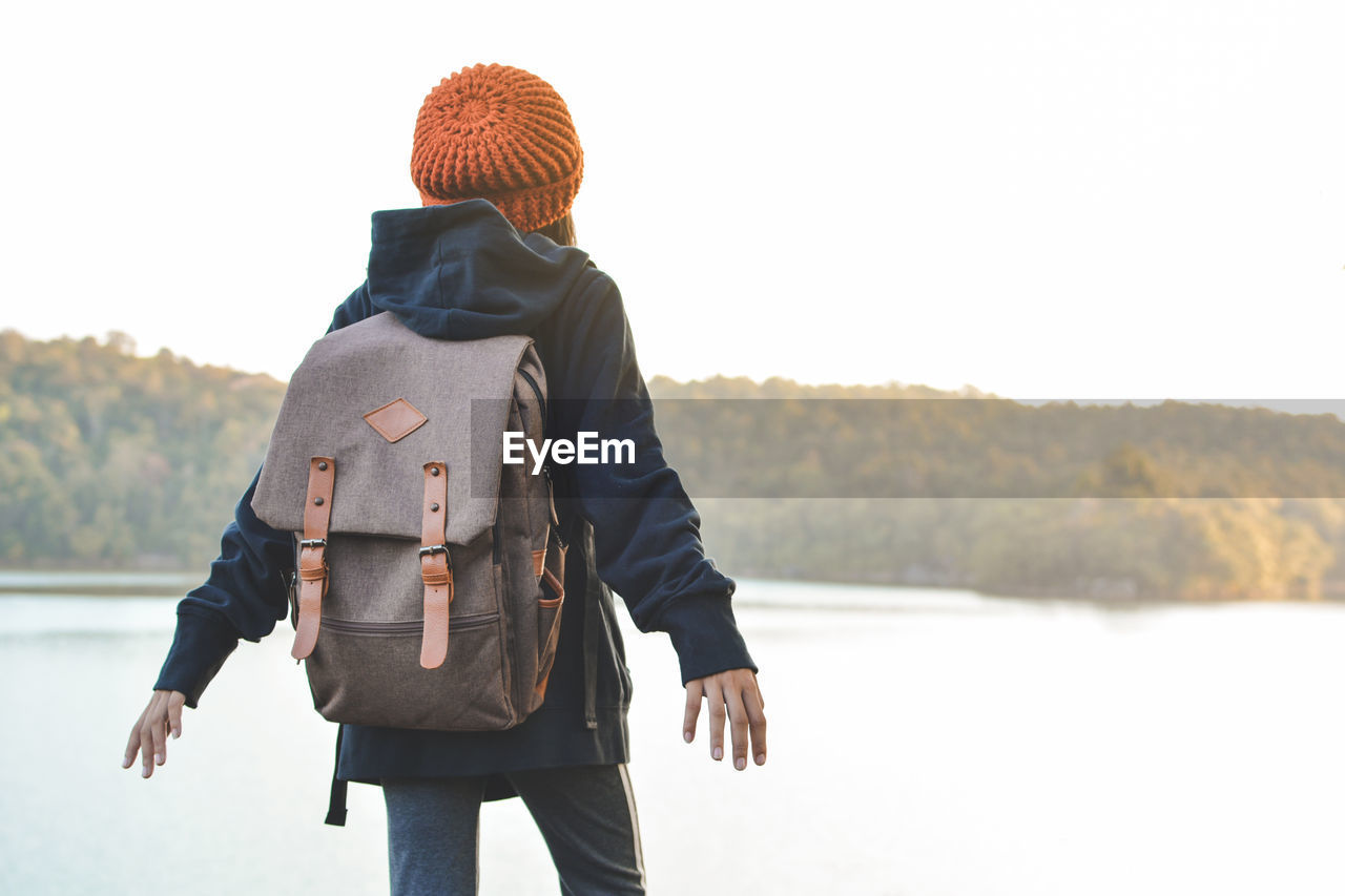 Rear View Of Girl Standing Against Lake And Sky