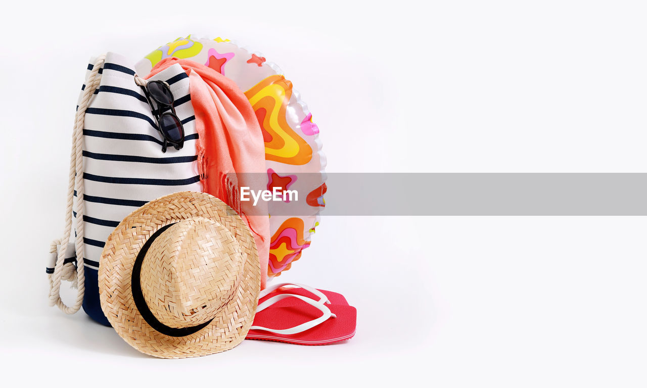 Inflatable ring and hat by bag against white background
