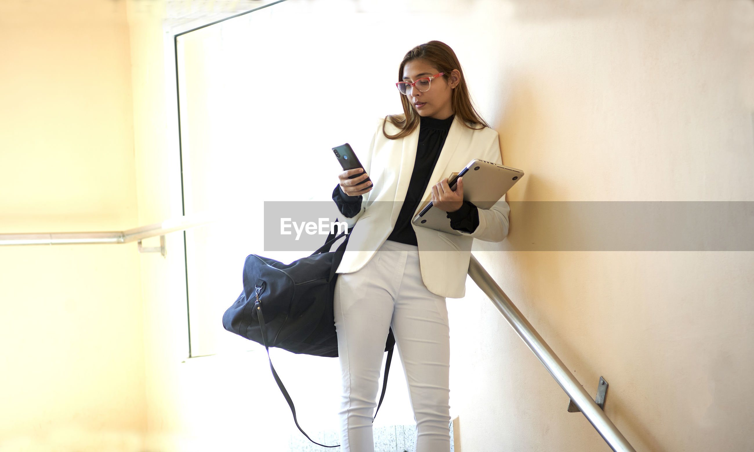 YOUNG WOMAN USING SMART PHONE WHILE STANDING AGAINST WALL