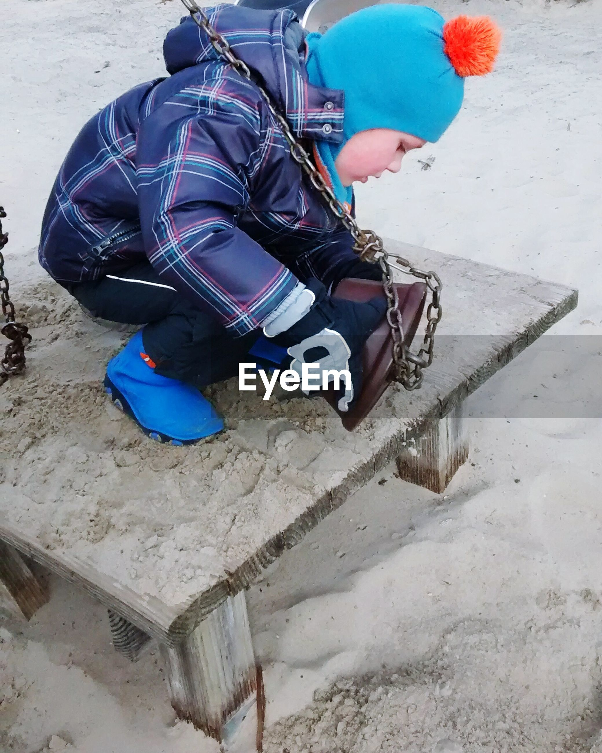 High angle view of boy crouching while pouring sand from bucket