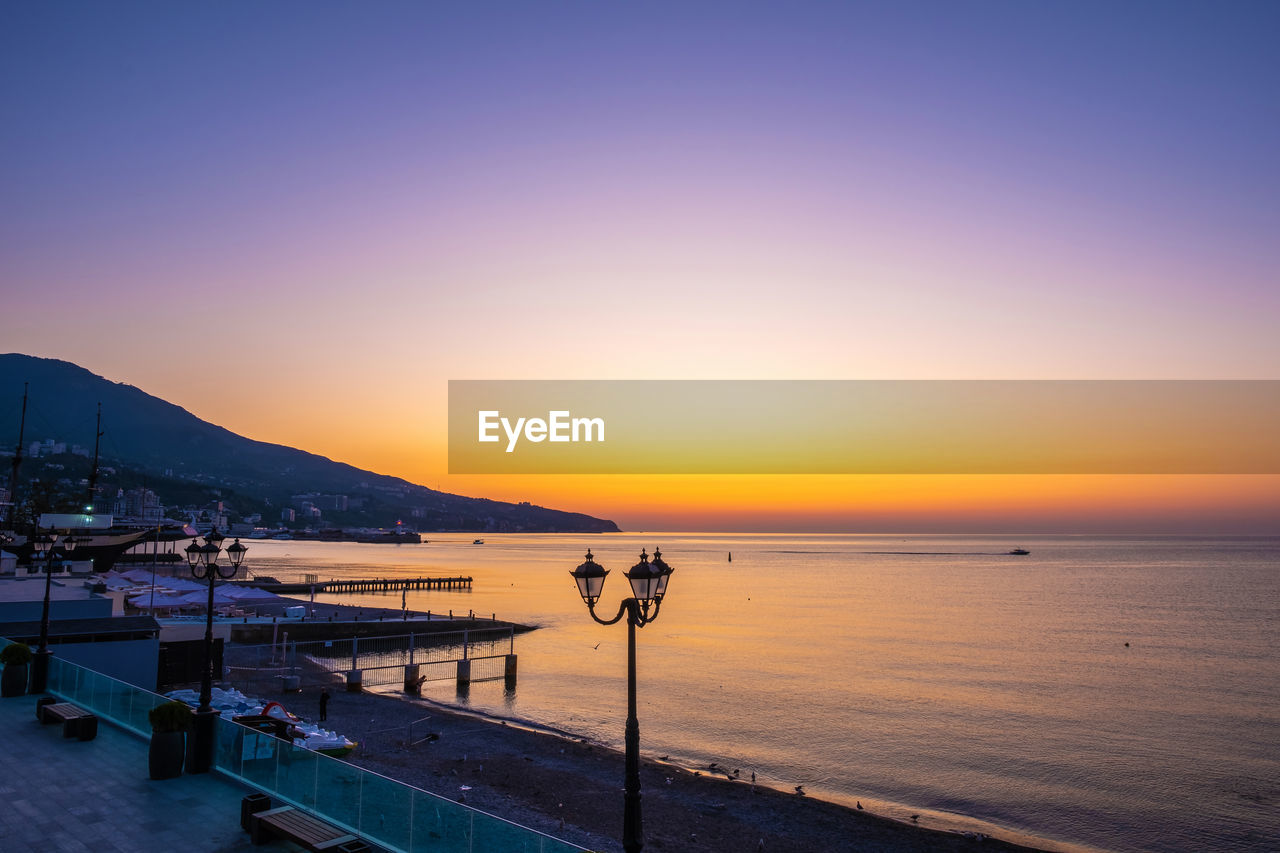 water, sky, sea, scenics - nature, sunset, beauty in nature, tranquility, horizon, copy space, tranquil scene, clear sky, nature, horizon over water, idyllic, orange color, beach, land, mountain, non-urban scene, no people, outdoors, promenade