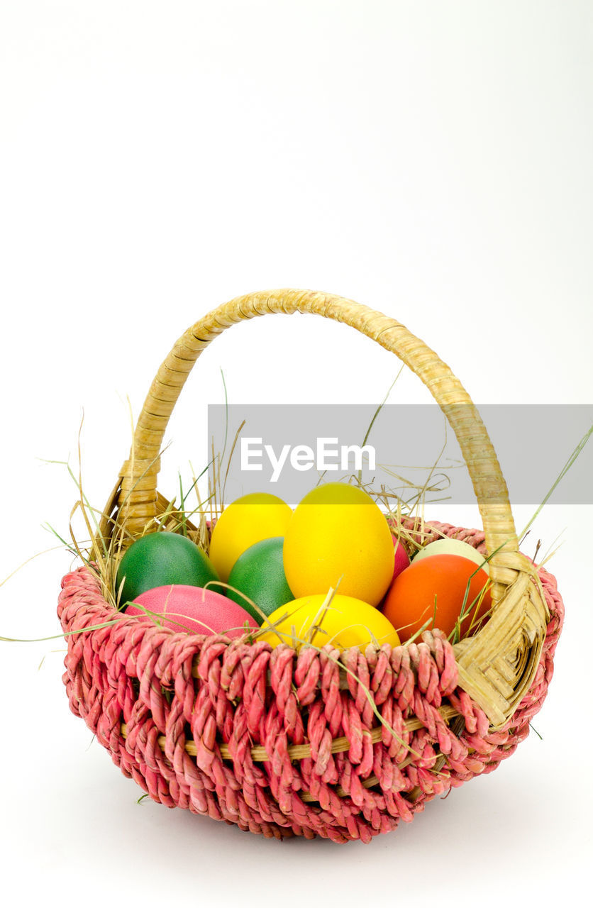 Close-up of colorful easter eggs in basket against white background