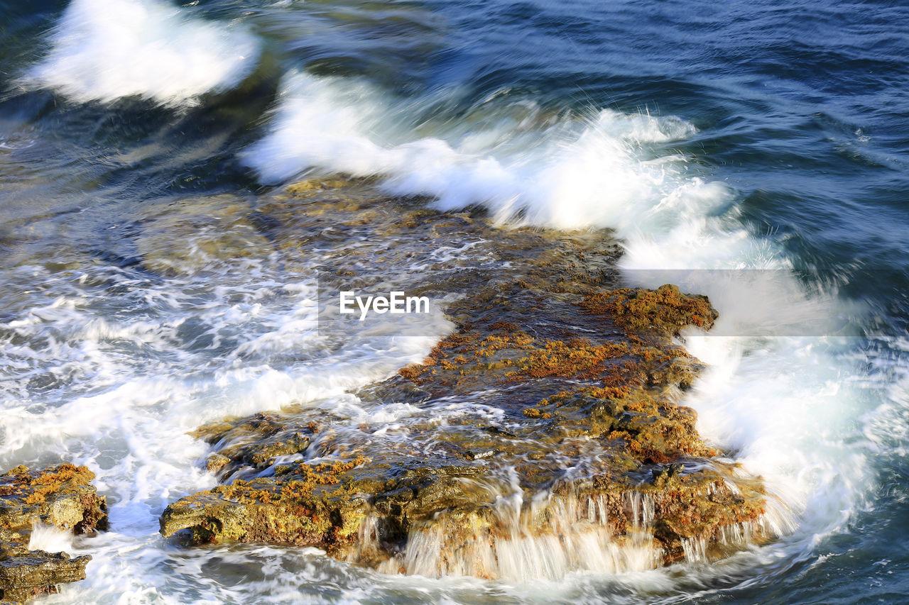VIEW OF WAVE SPLASHING ON ROCKS