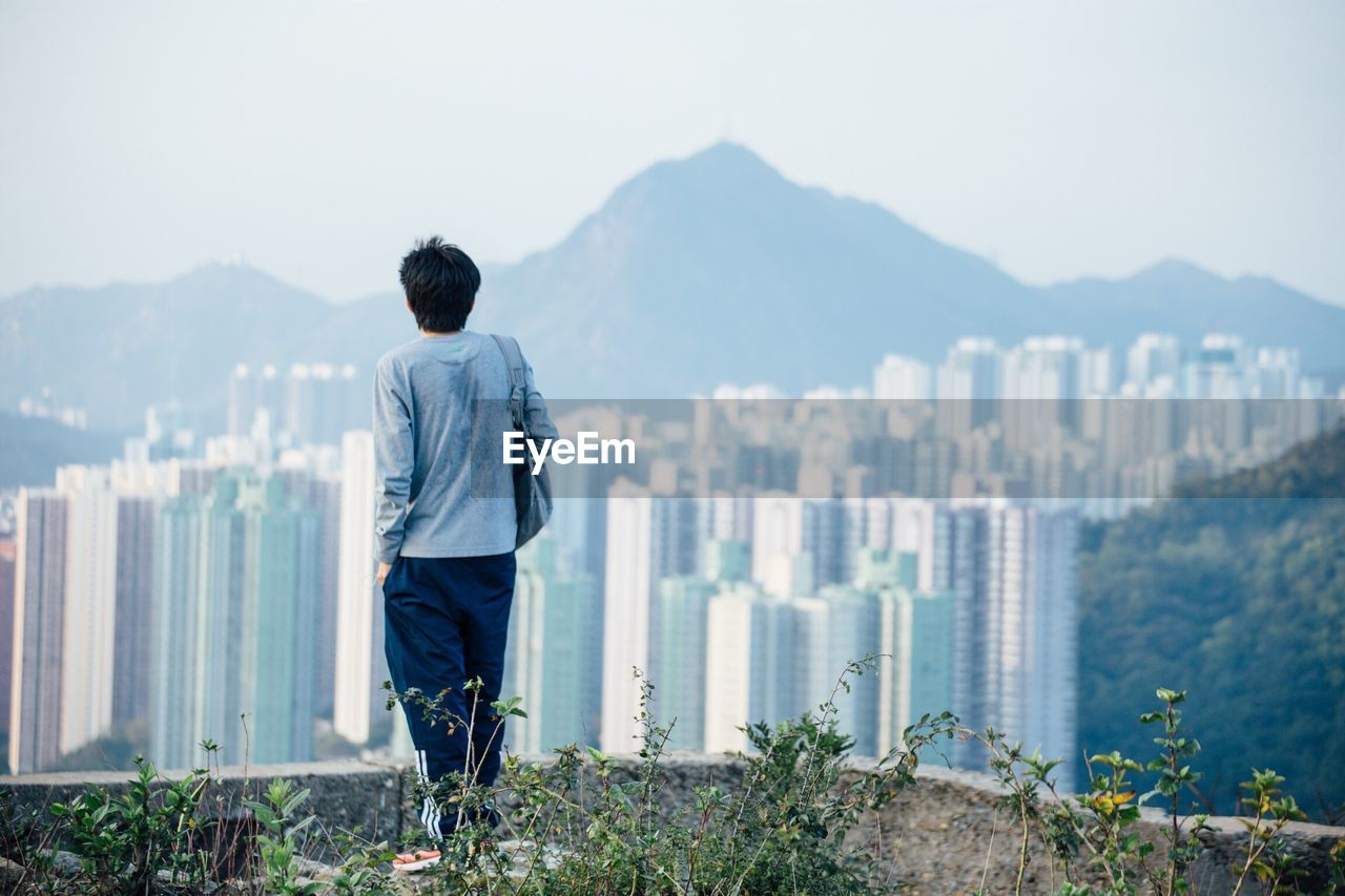 mountain, rear view, real people, one person, casual clothing, day, leisure activity, outdoors, standing, nature, lifestyles, full length, clear sky, sea, men, mountain range, beauty in nature, sky, water, architecture, young adult, city, people