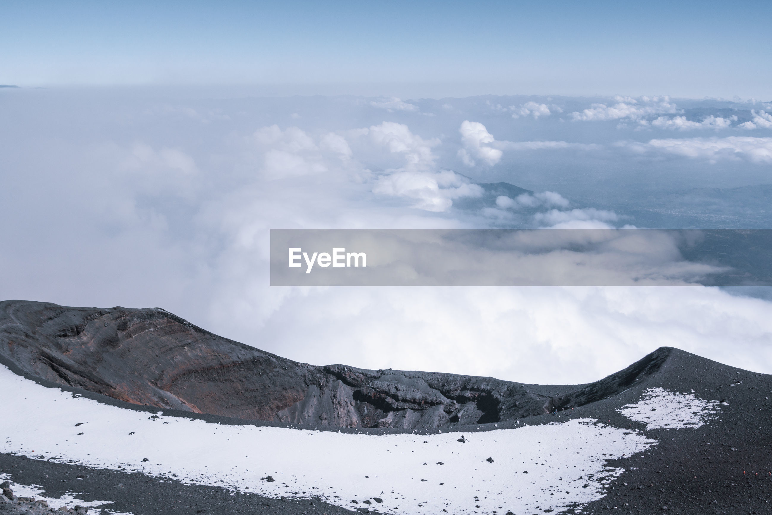 Scenic view of volcanic crater with snow against sky