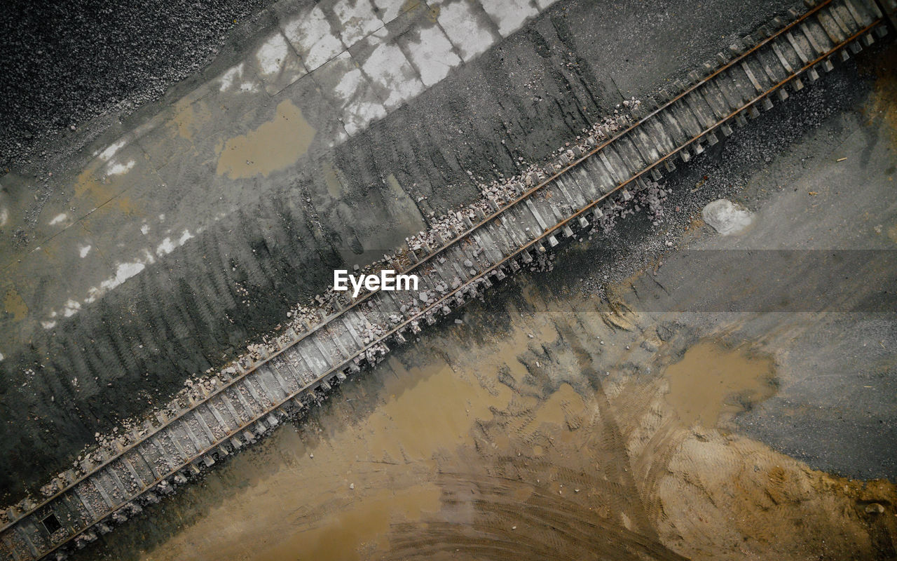 HIGH ANGLE VIEW OF WATER FLOWING THROUGH WET METAL