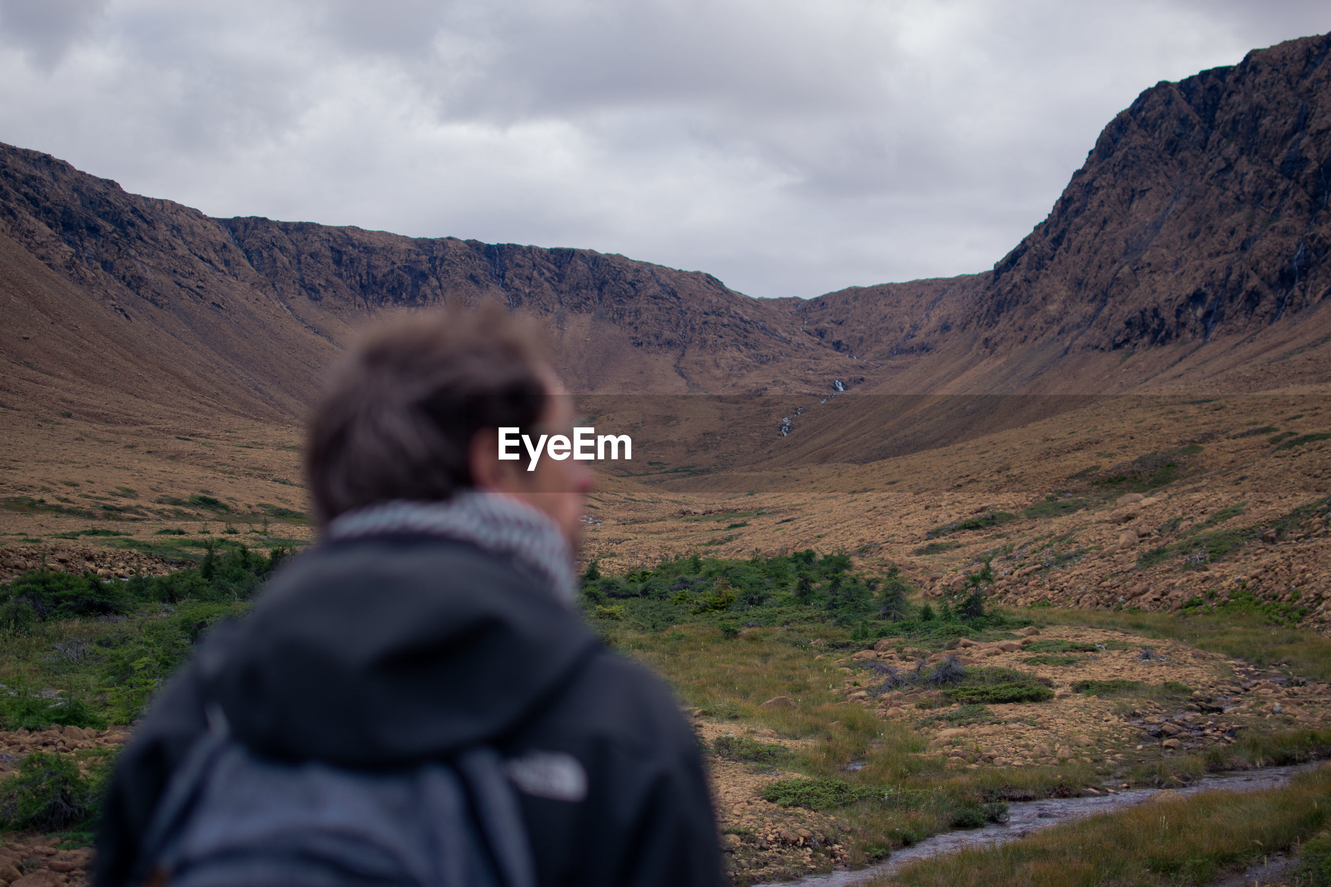 Rear view of man standing by mountains against cloudy sky