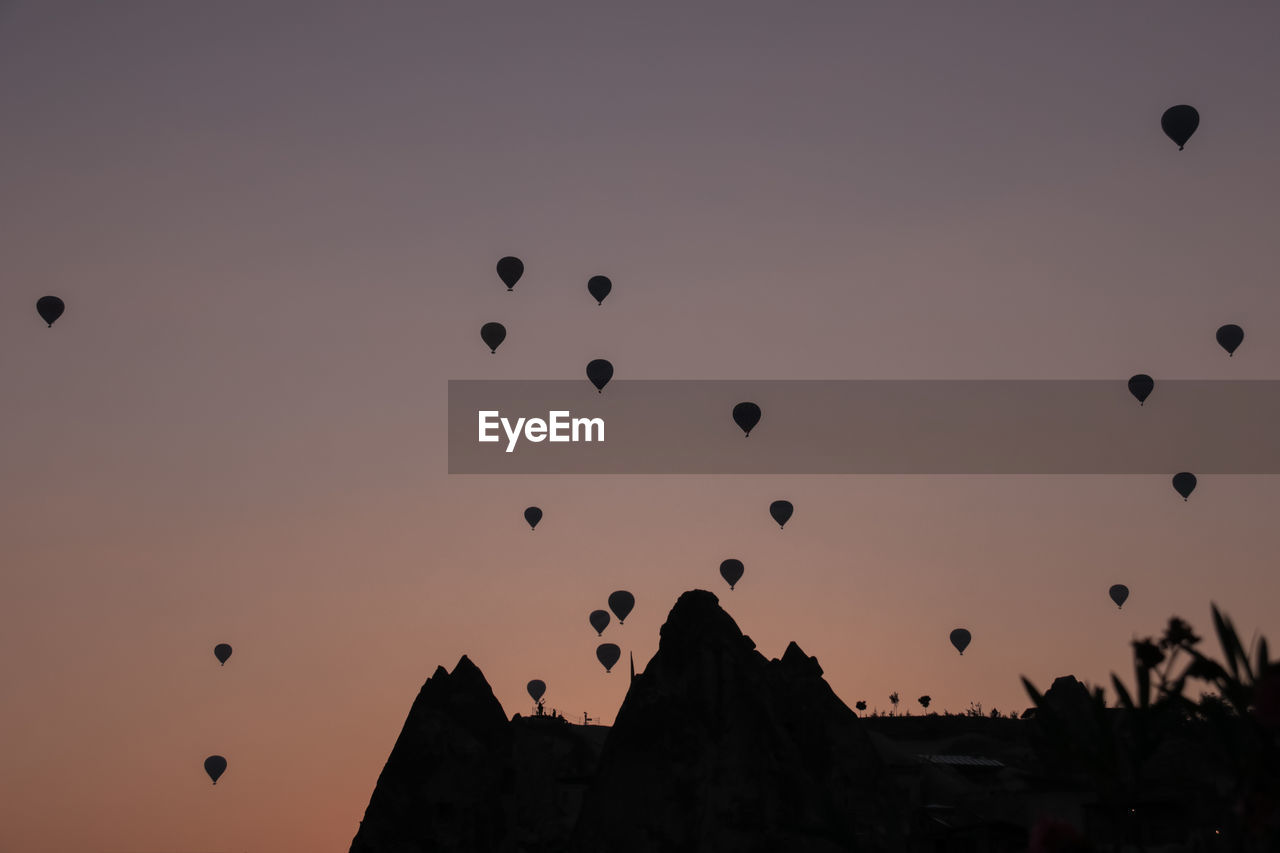 sky, sunset, balloon, silhouette, air vehicle, hot air balloon, flying, mid-air, nature, low angle view, beauty in nature, orange color, scenics - nature, adventure, no people, tranquil scene, architecture, outdoors, tranquility, clear sky, ballooning festival
