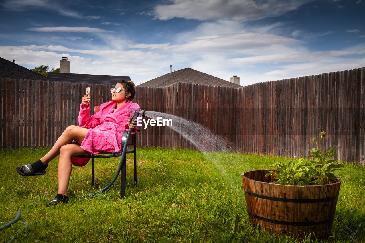 Woman Sitting On Seat In Yard Against Sky