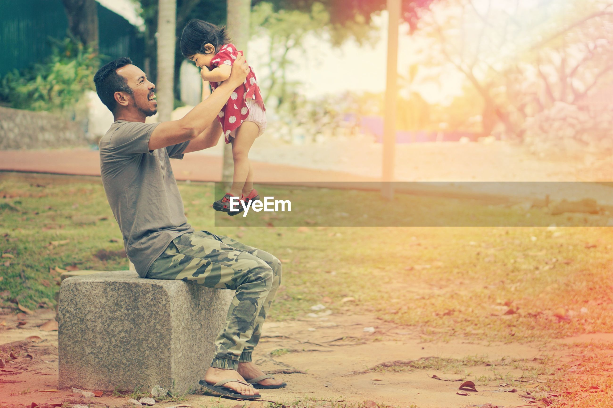 Side view of on father holding daughter while sitting at park