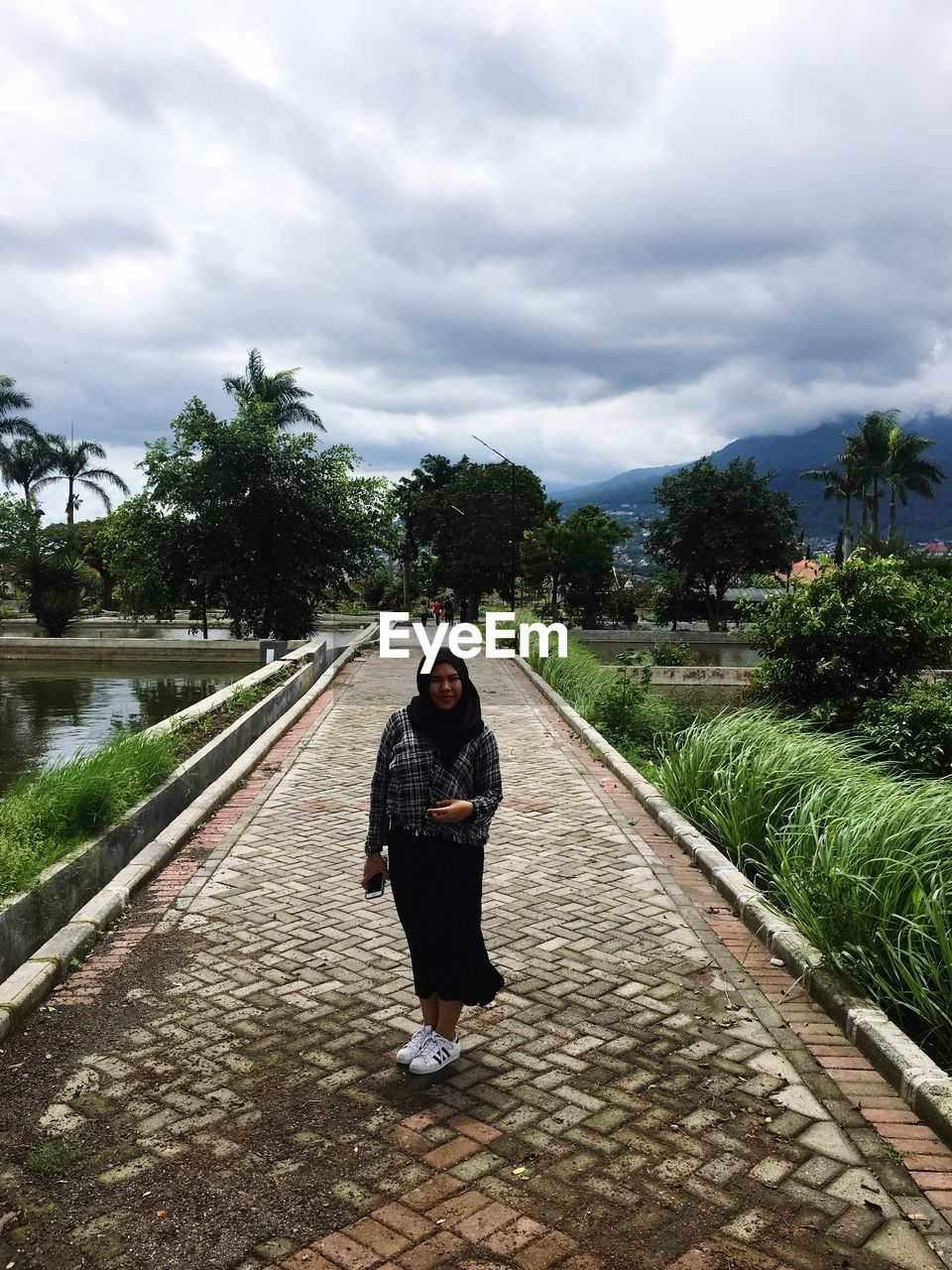 cloud - sky, sky, full length, one person, plant, tree, real people, nature, rear view, direction, the way forward, casual clothing, transportation, lifestyles, leisure activity, day, footpath, standing, diminishing perspective, outdoors