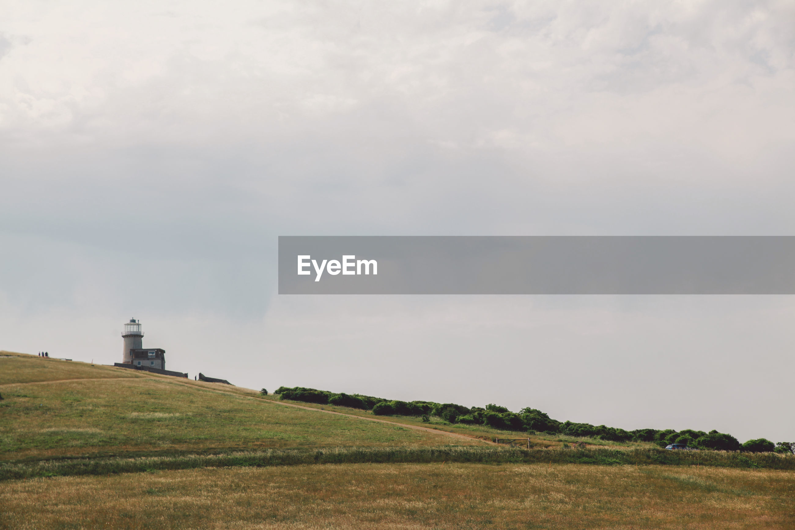 Distant view of lighthouse on field against cloudy sky