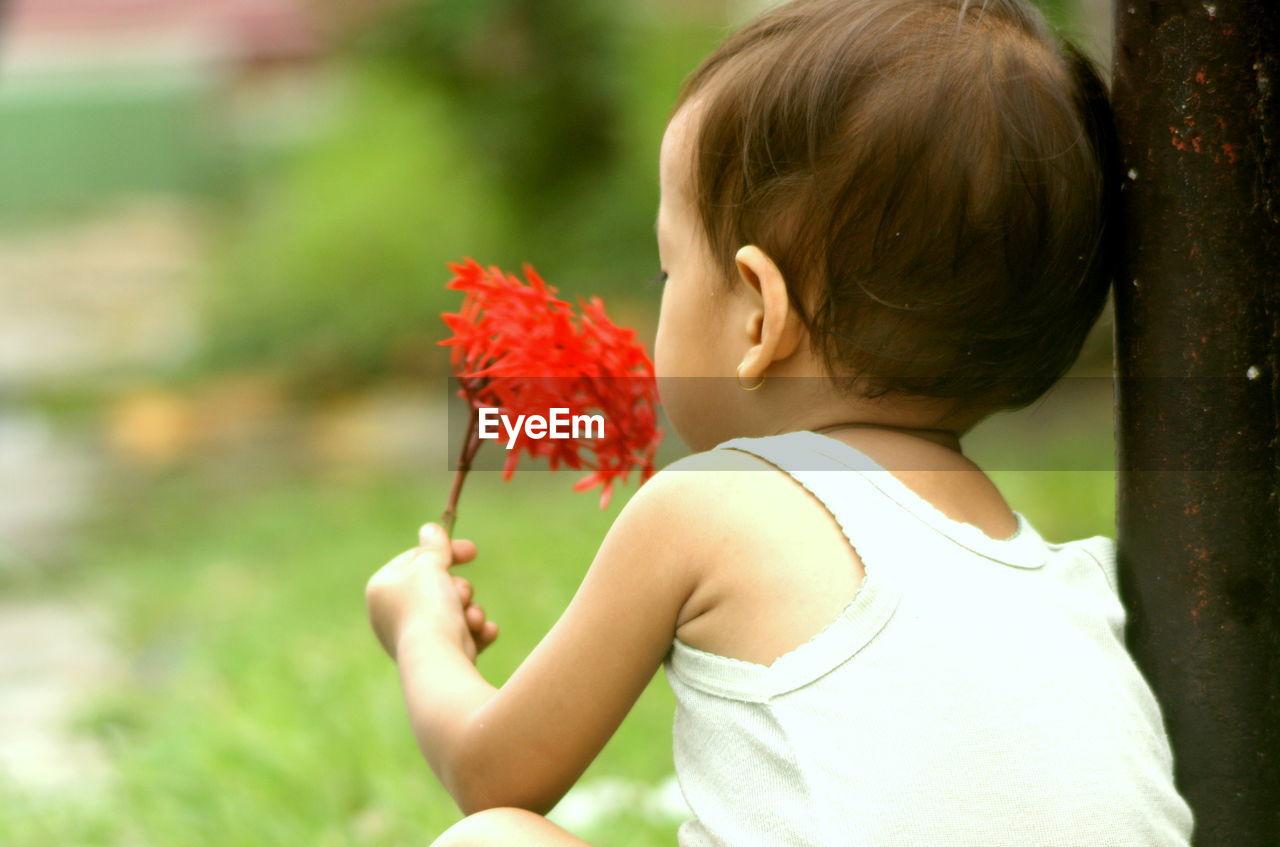 Girl holding ixora flowers in park