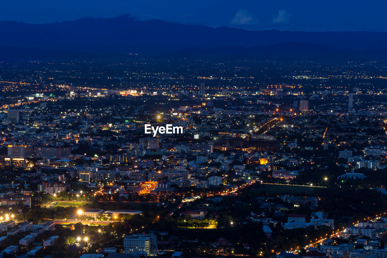 building exterior, city, cityscape, architecture, illuminated, built structure, night, building, no people, residential district, sky, high angle view, nature, mountain, aerial view, city life, outdoors, dusk, office building exterior, townscape
