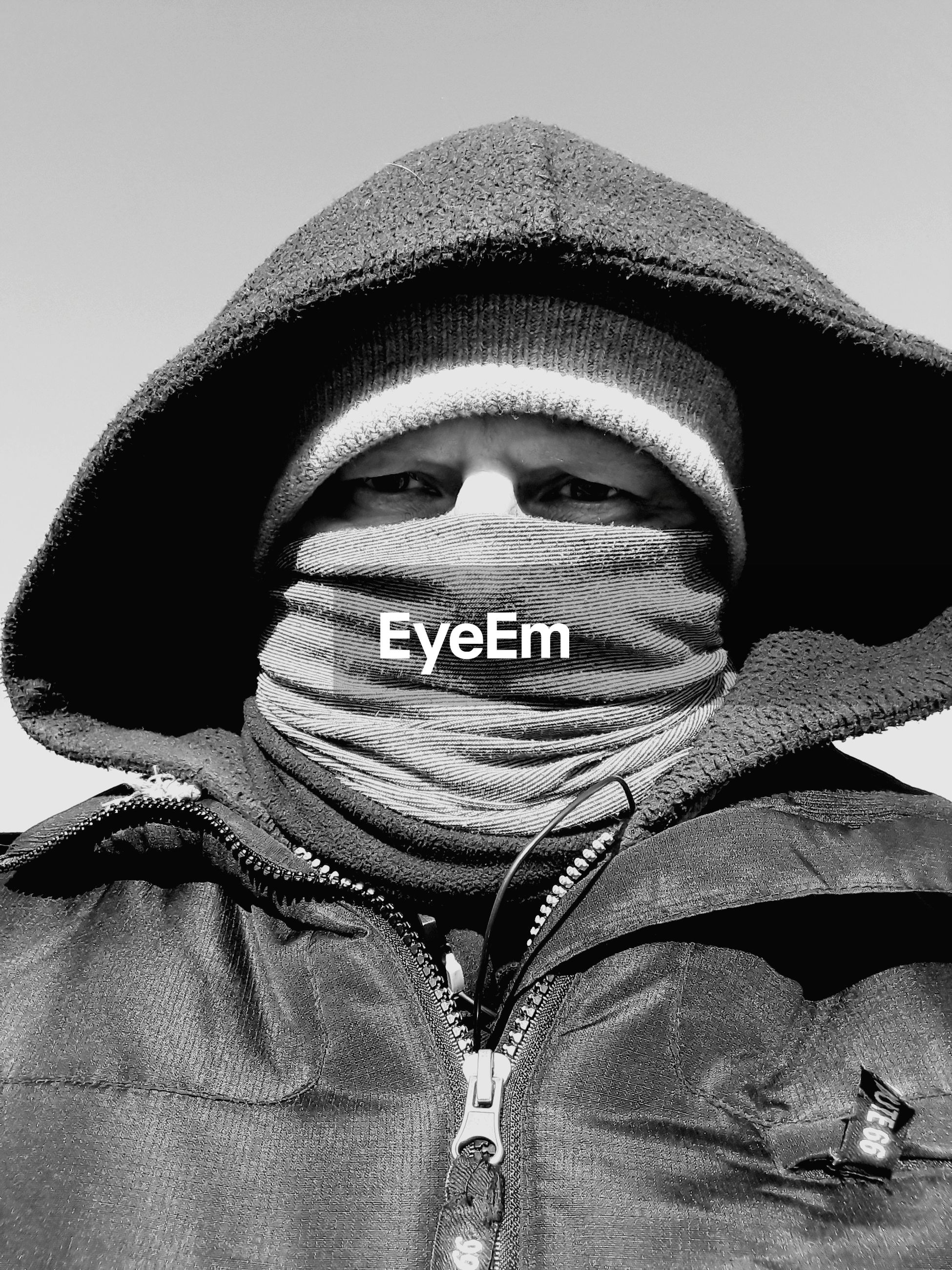Low angle portrait of man wearing warm clothing against clear sky