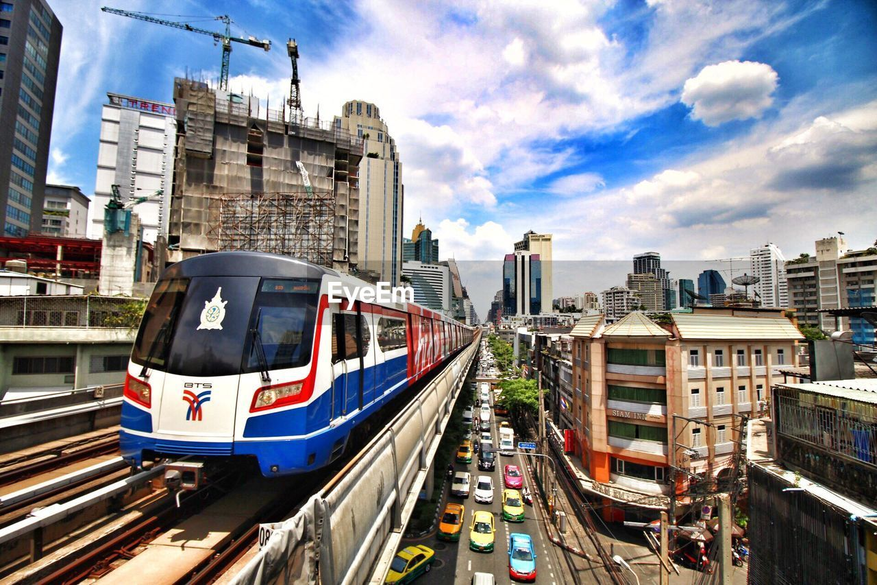 View of sky train by buildings and cars in city