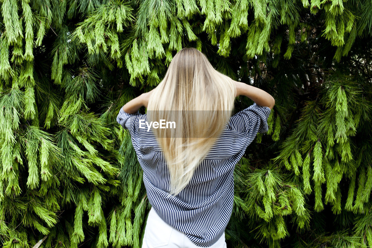 one person, green color, rear view, women, adult, hair, plant, blond hair, growth, nature, hairstyle, long hair, day, real people, standing, leisure activity, three quarter length, leaf, waist up, obscured face