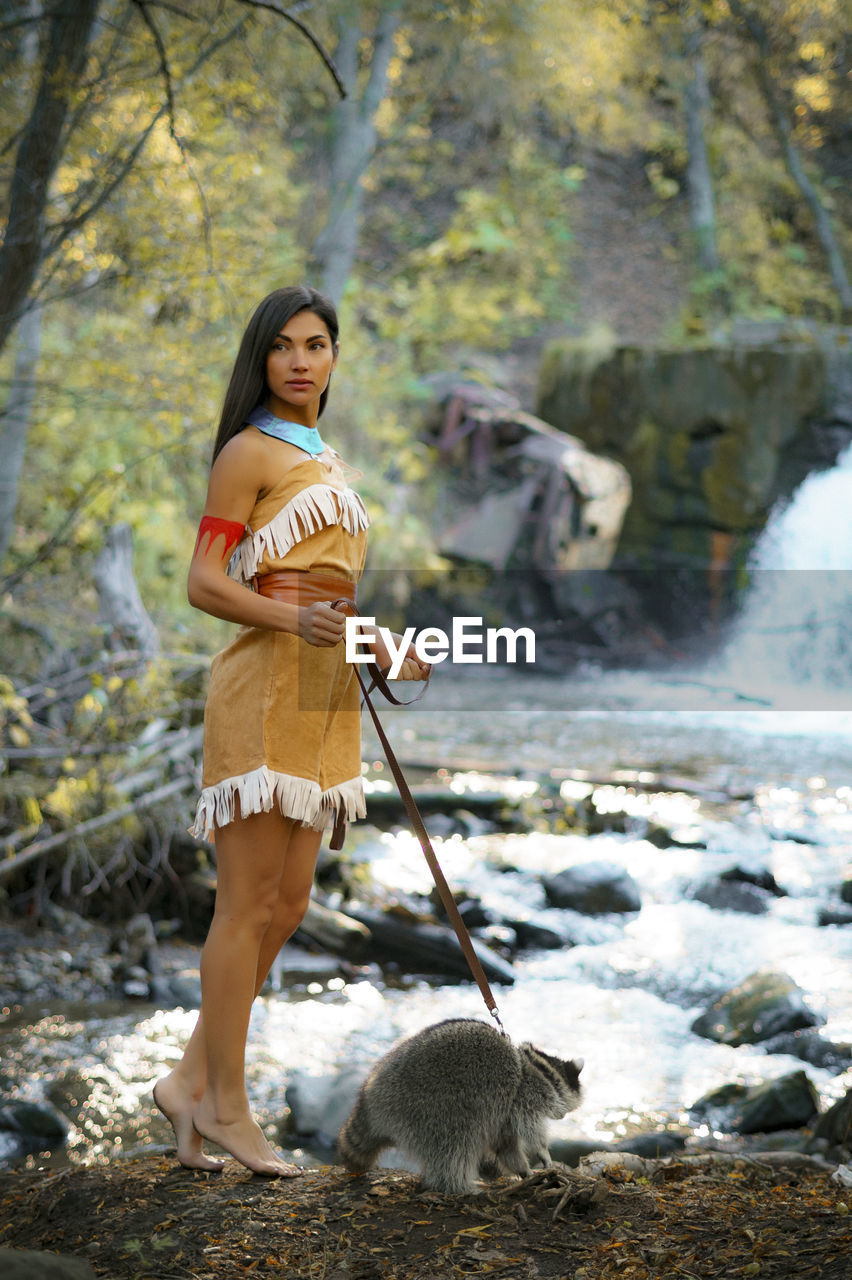 Young Woman In Traditional Clothing Looking Away While Standing By Raccoon In Forest