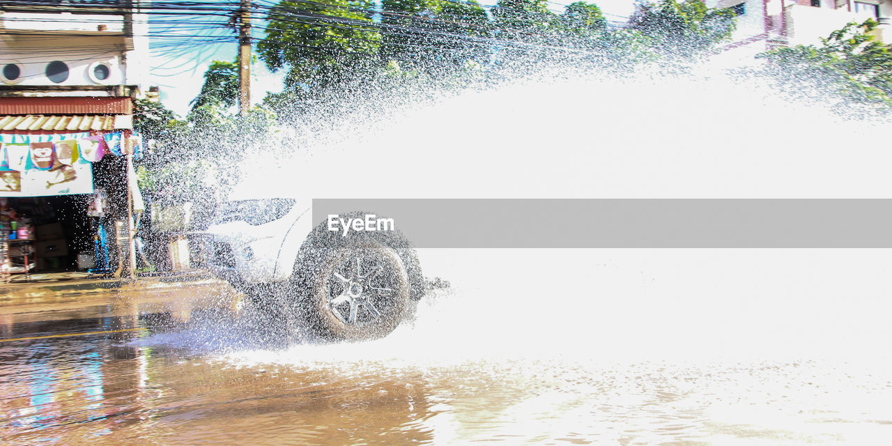 water, motion, transportation, nature, mode of transportation, day, splashing, land vehicle, waterfront, architecture, spraying, wheel, speed, sport, outdoors, city, tire, building exterior, built structure
