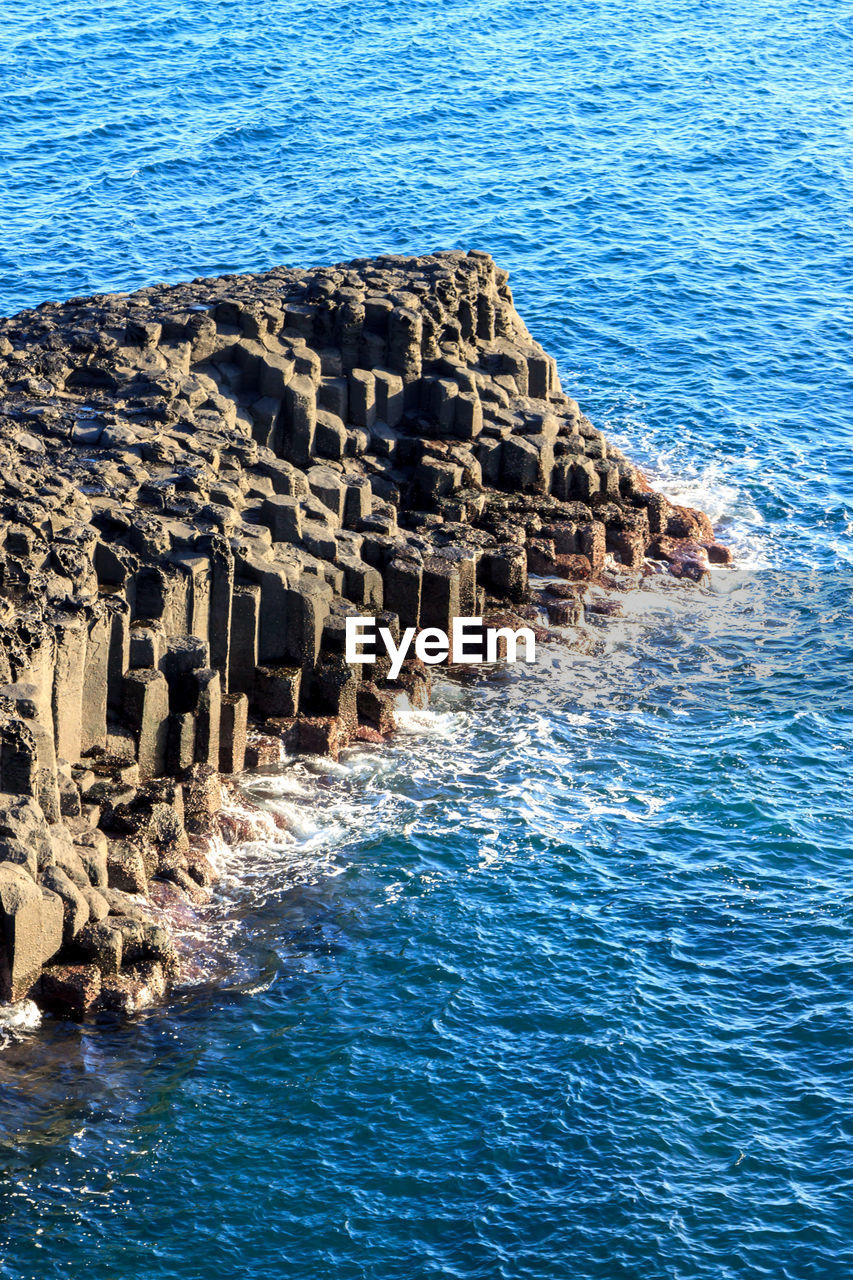 sea, water, no people, architecture, nature, day, history, waterfront, built structure, blue, the past, high angle view, outdoors, wave, beauty in nature, sunlight, scenics - nature, solid, rock, ancient civilization, groyne