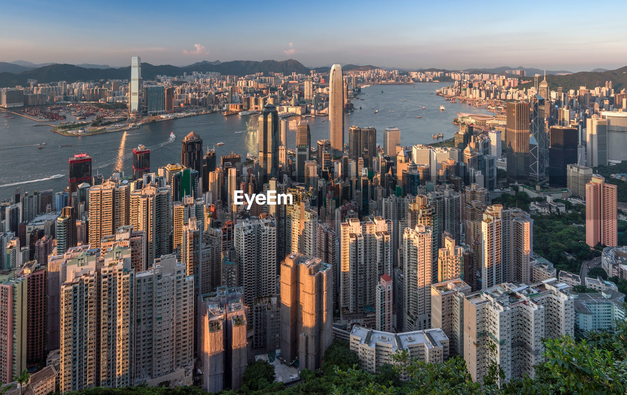 building exterior, cityscape, built structure, office building exterior, architecture, city, building, skyscraper, sky, modern, crowd, tall - high, residential district, travel destinations, water, crowded, nature, tower, downtown district, development, financial district, outdoors