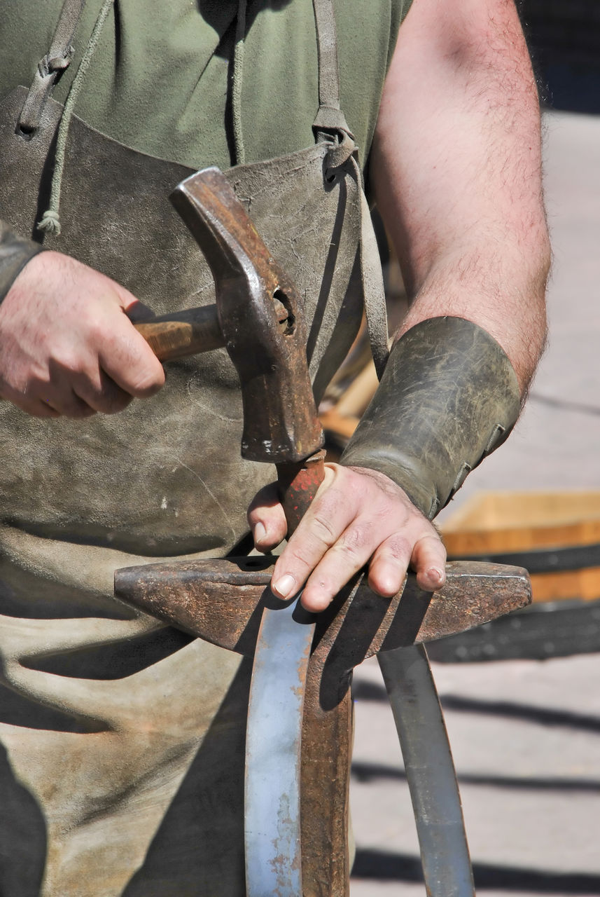 one person, metal, holding, human hand, real people, hand, men, midsection, day, working, protection, hand tool, tool, safety, work tool, close-up, occupation, skill, security